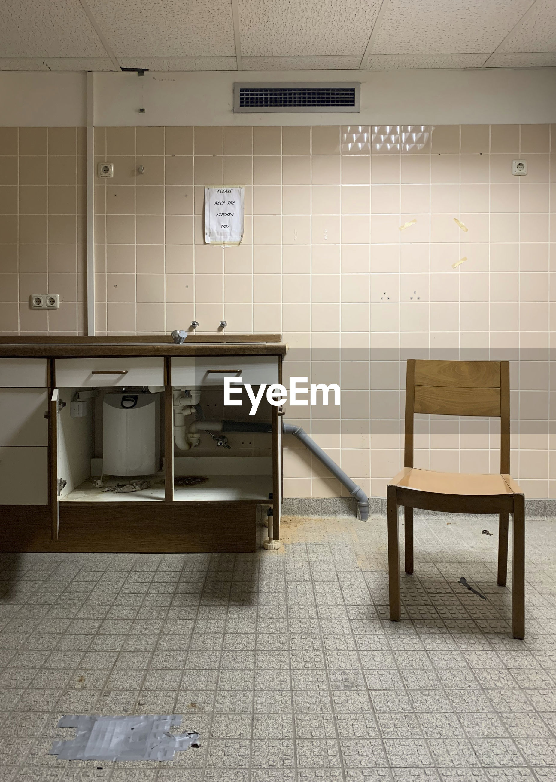 EMPTY CHAIRS AND TABLE AGAINST TILED WALL