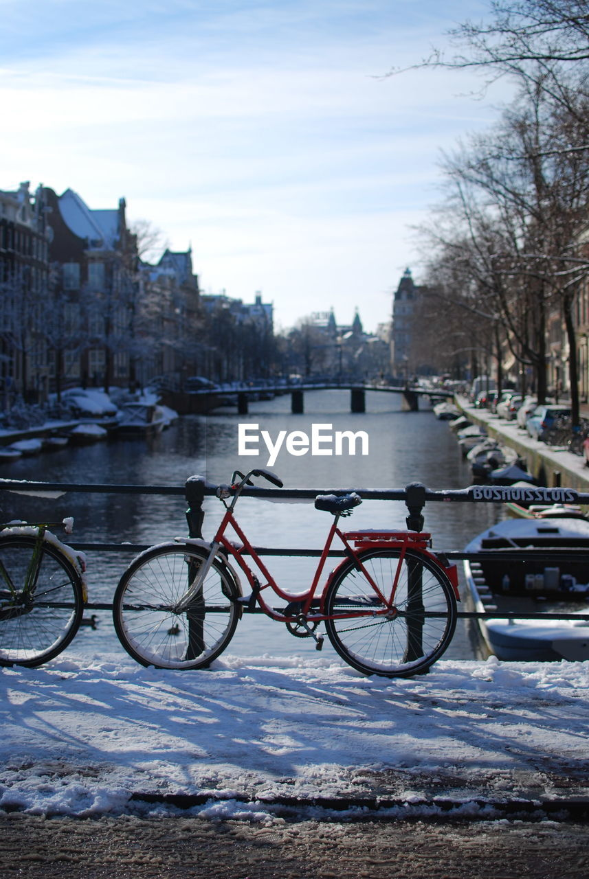 transportation, mode of transportation, bicycle, architecture, water, land vehicle, building exterior, built structure, city, nature, snow, sky, cold temperature, stationary, winter, river, parking, tree, no people, outdoors