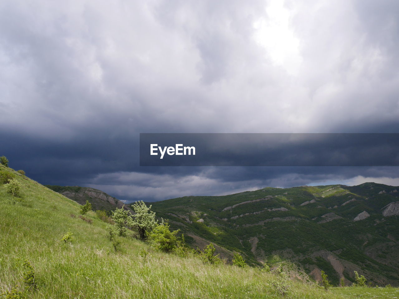 Scenic view of grassy mountain against cloudy sky