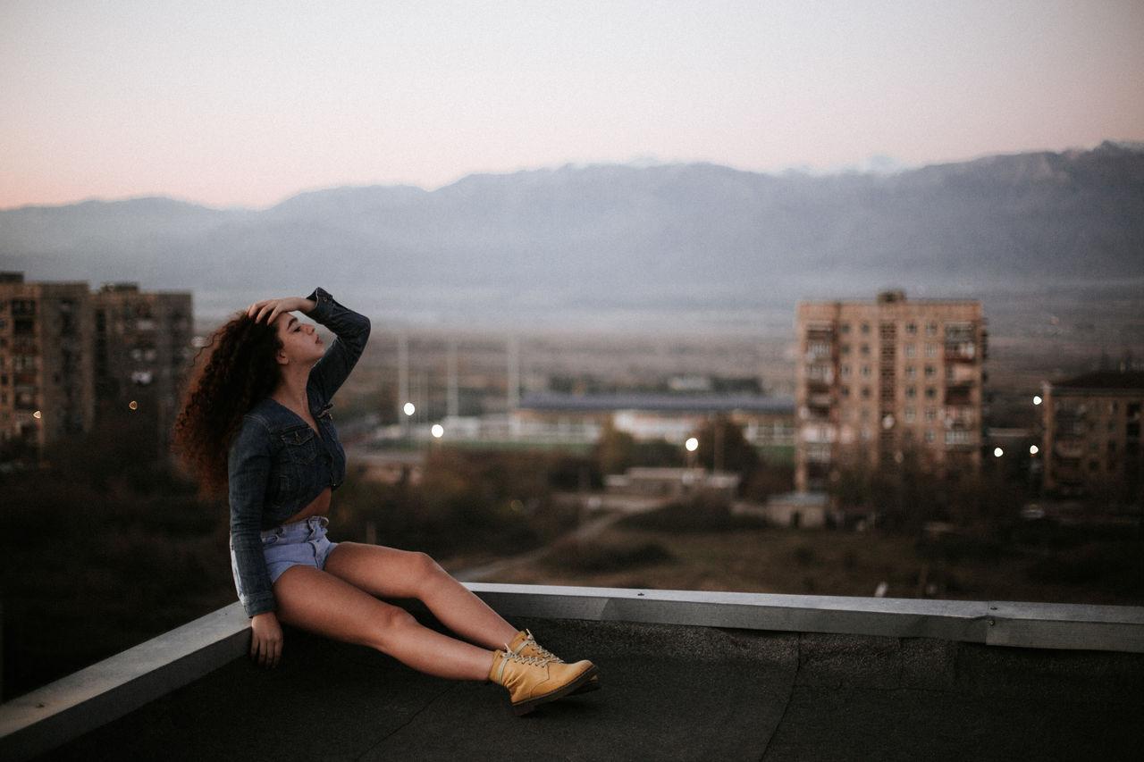 Woman sitting on terrace in city