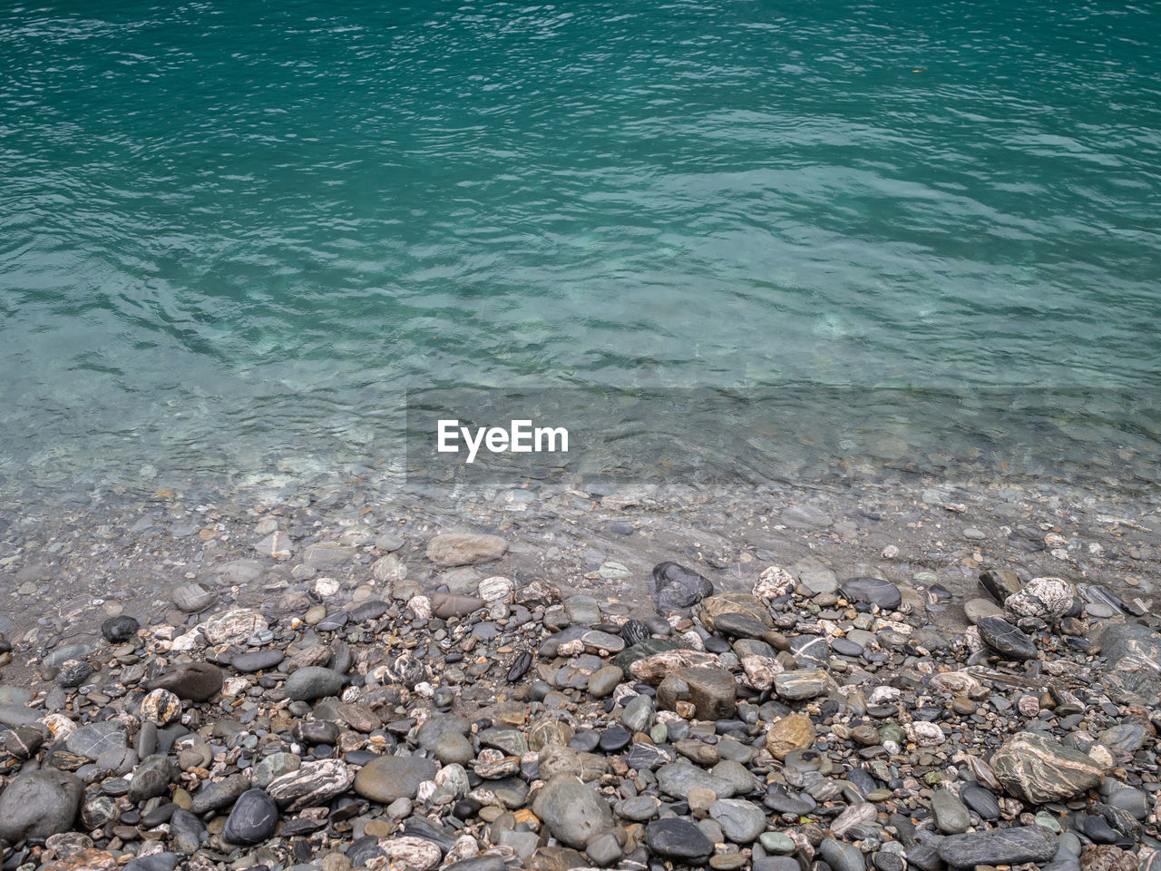 water, sea, beauty in nature, rock, solid, land, nature, day, no people, tranquility, rock - object, tranquil scene, scenics - nature, stone, beach, outdoors, high angle view, idyllic, animal wildlife, pebble, turquoise colored, shallow, purity