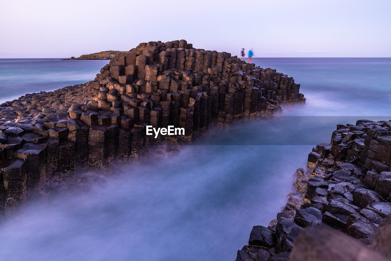 High Angle View Of Rock Formations Amidst Sea Against Sky