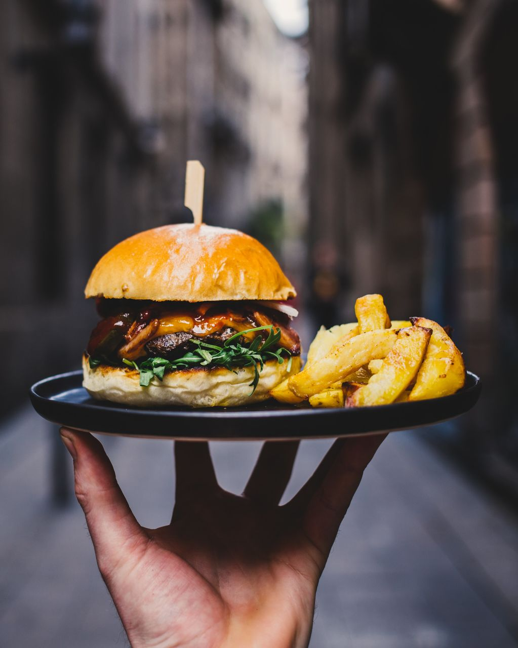 Close-Up Of Person Holding Burger Outdoors