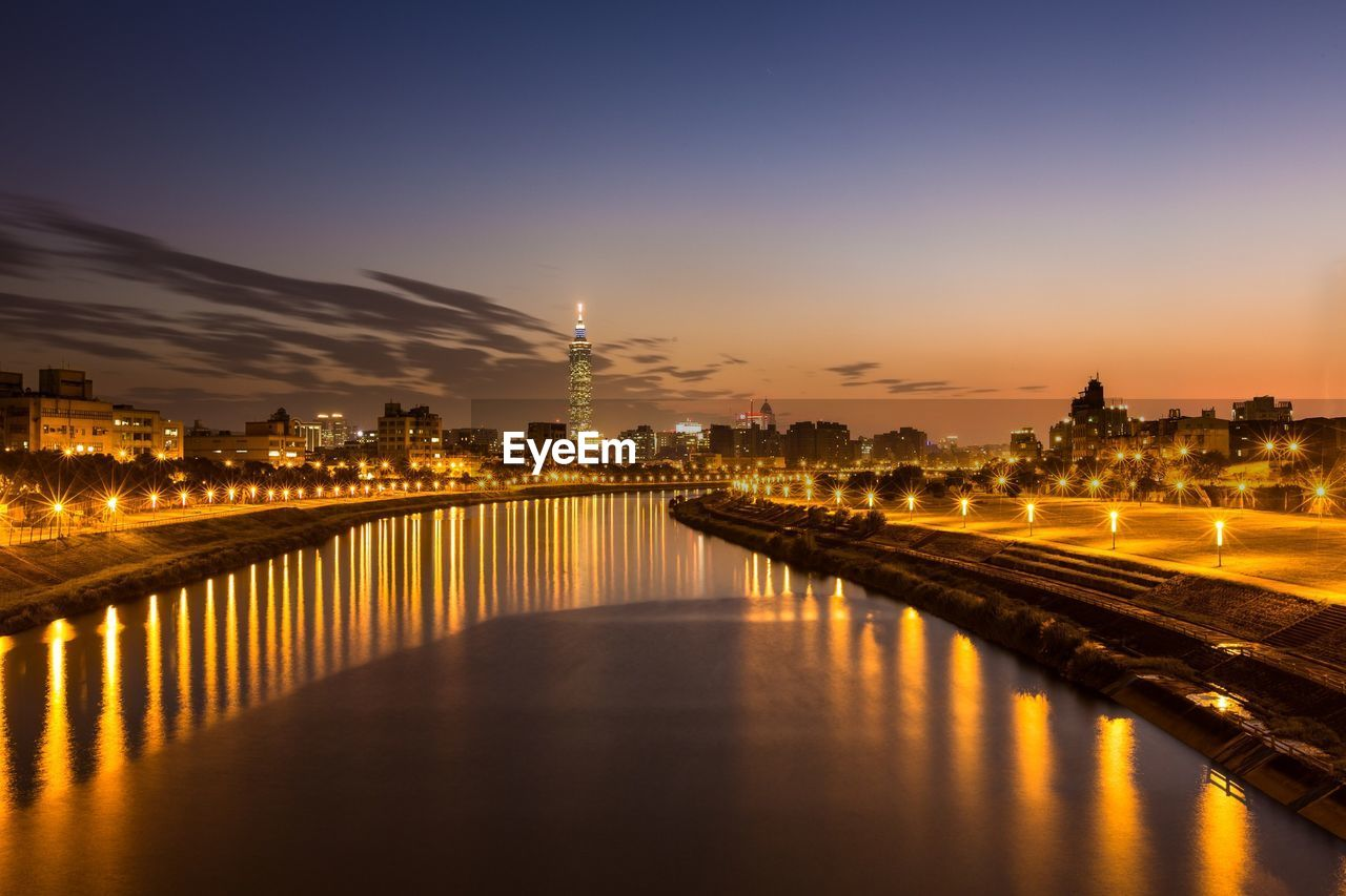 Canal Amidst Illuminated Lighting Equipment Against Sky At Dusk