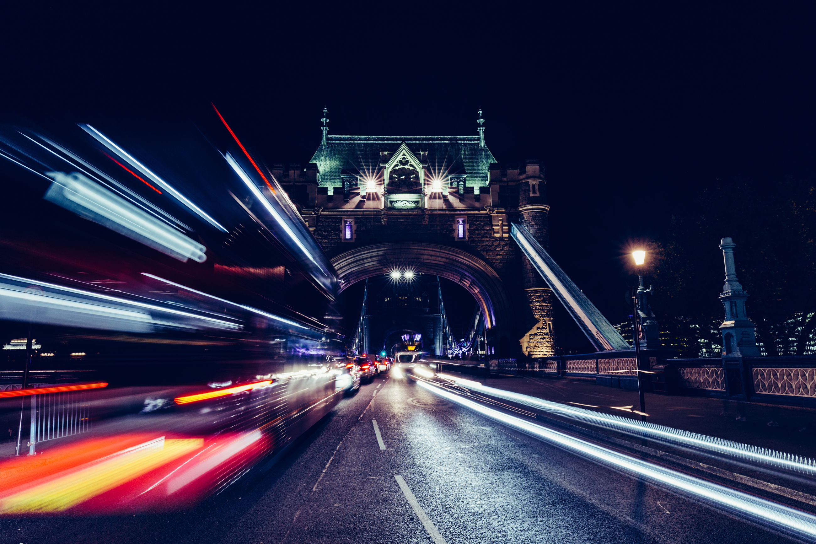 Blurred Motion Of Vehicle On Tower Bridge In City At Night