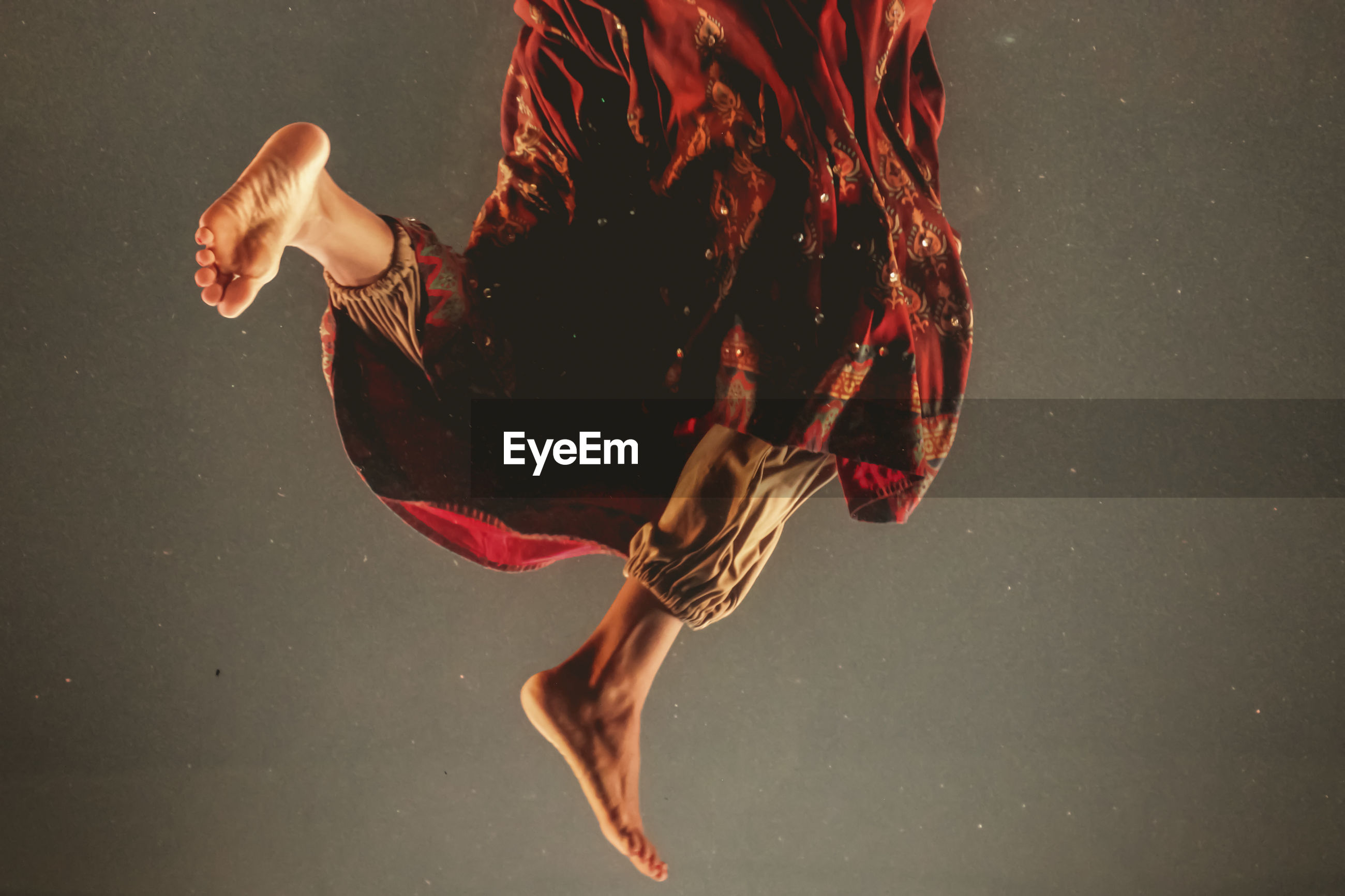 Low section of woman jumping against gray background
