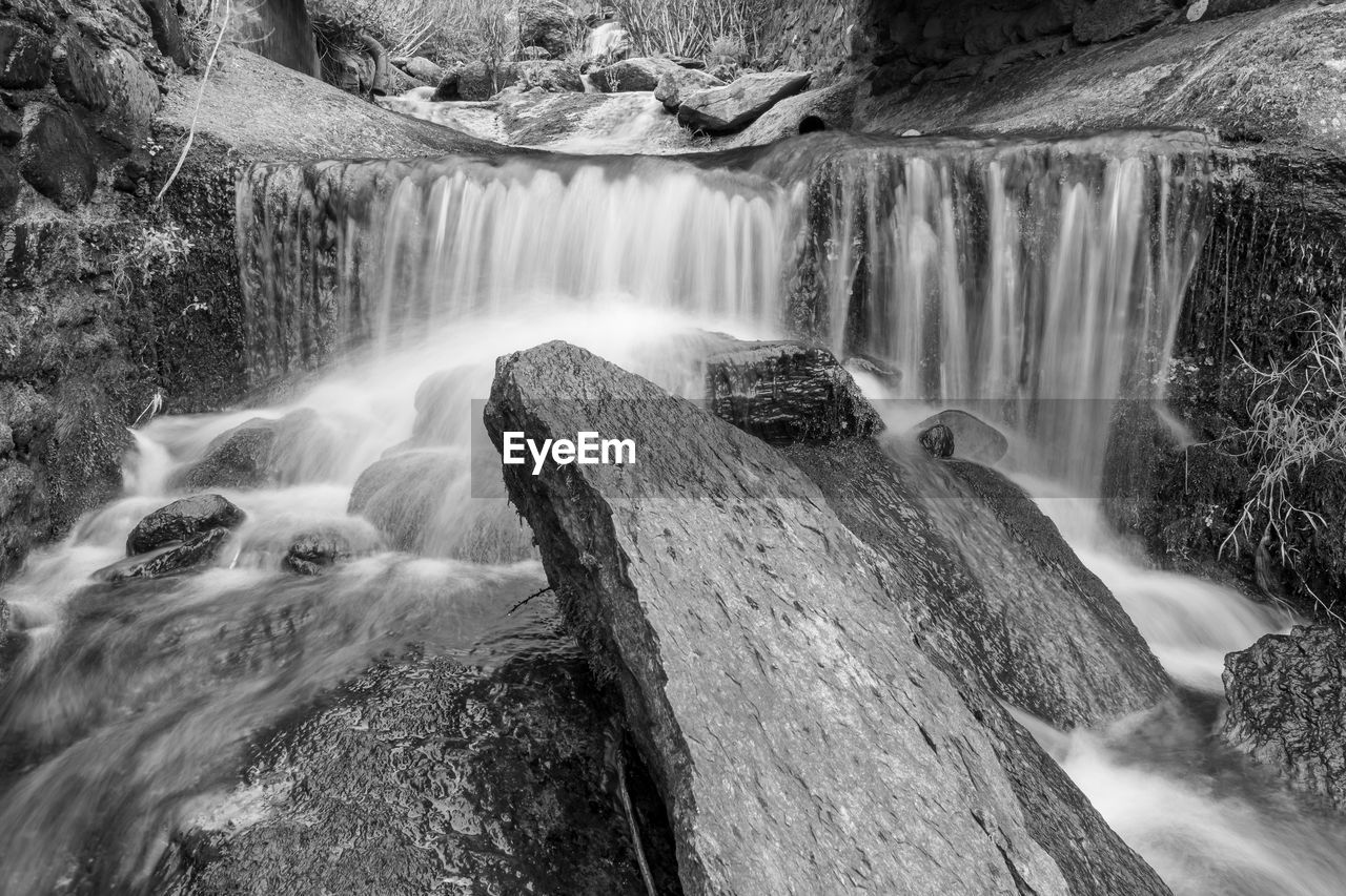 VIEW OF WATERFALL WITH ROCKS IN FOREGROUND