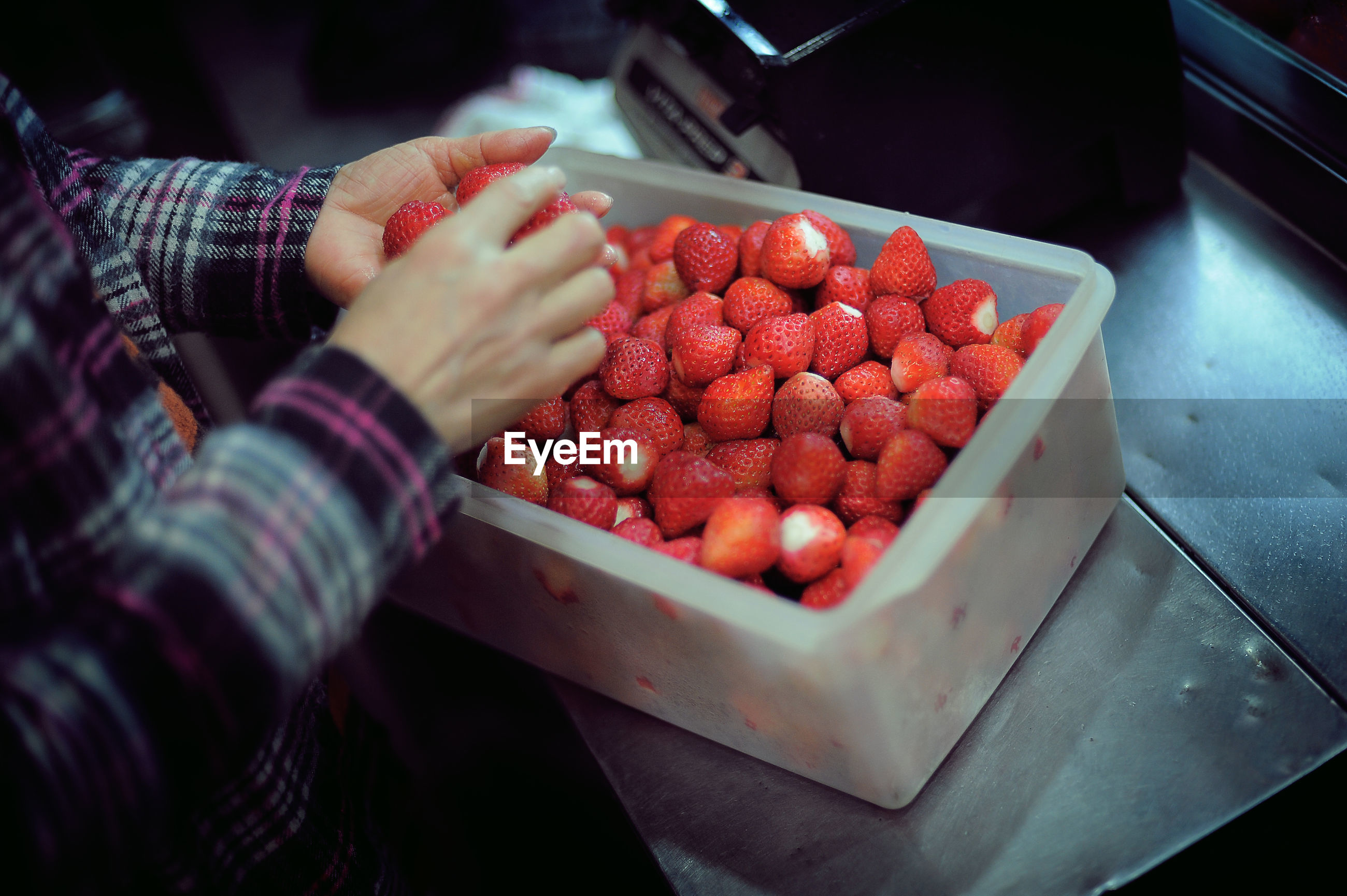 Midsection of man selling strawberries at market stall during night