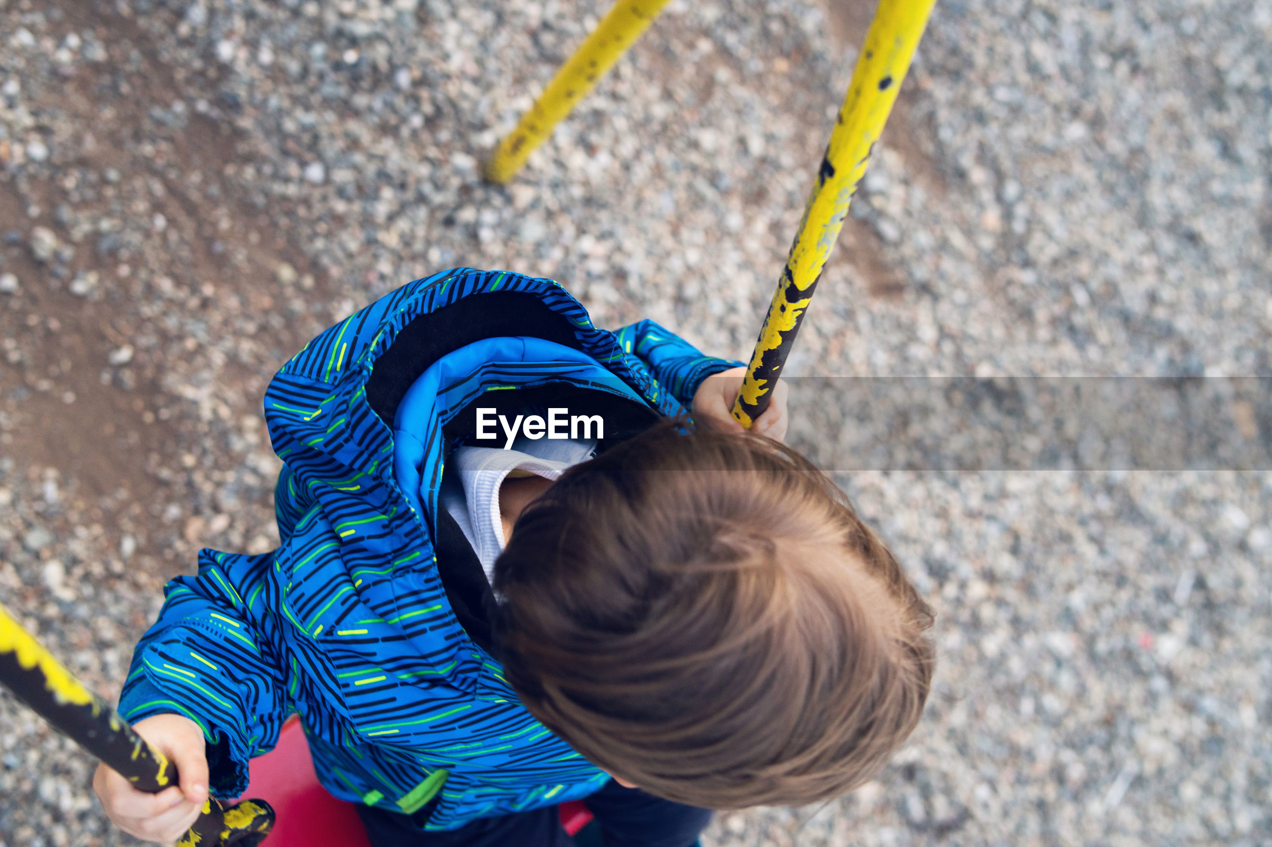 High angle view of boy swinging at playground