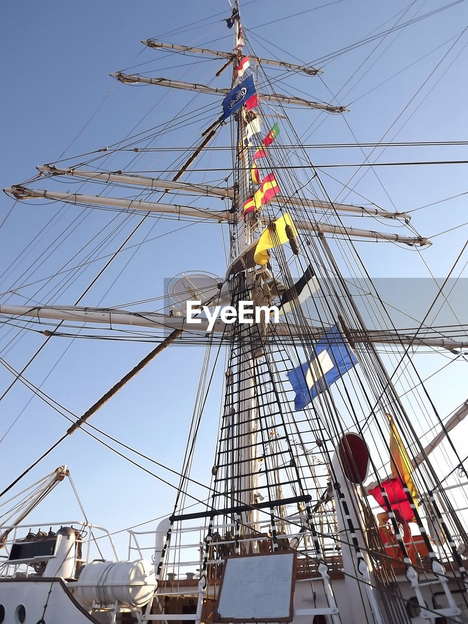 low angle view, real people, day, sky, transportation, nautical vessel, mast, men, outdoors, rigging, helmet, headwear, clear sky, working, occupation, architecture, one person, tall ship, teamwork, hardhat, sailing ship, people