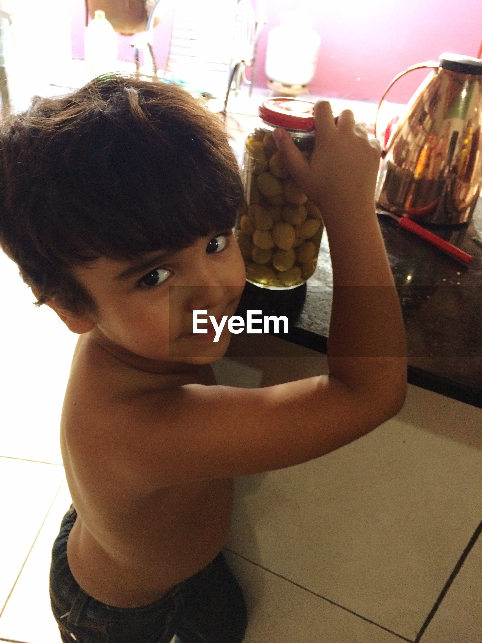 Portrait of shirtless boy holding olives in jar on table at home