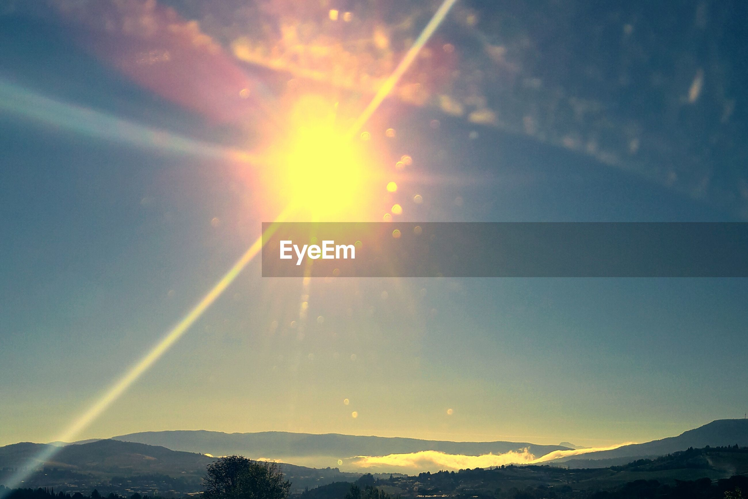 SCENIC VIEW OF MOUNTAINS AGAINST BRIGHT SUN IN SKY