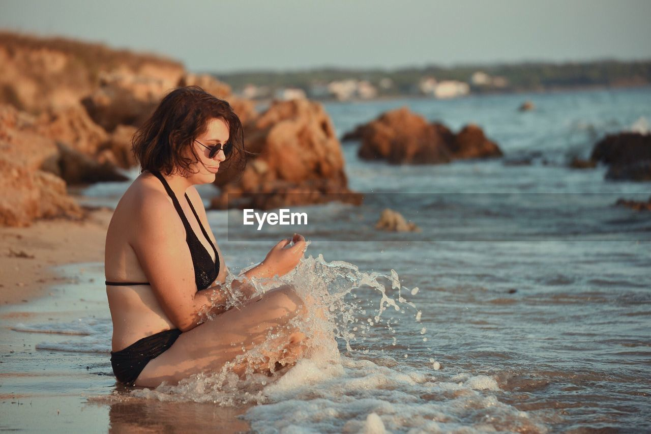 Young Woman On Shore At Beach Against Sky