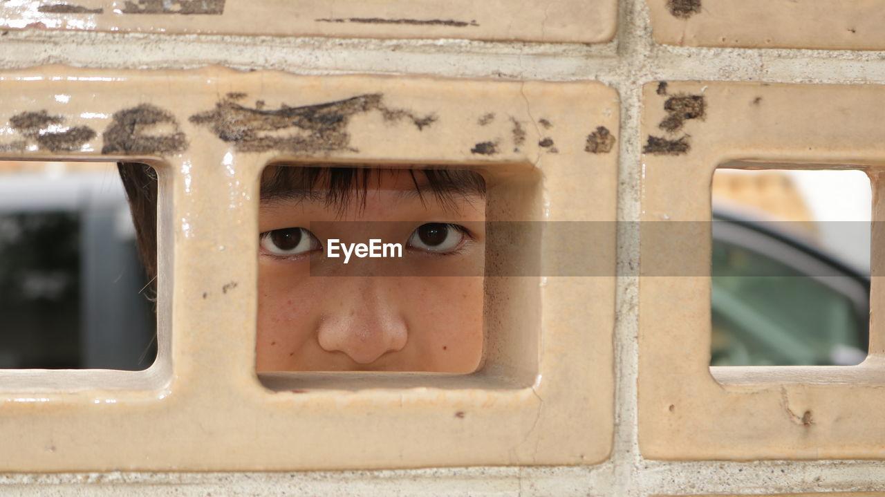 Portrait of boy looking through wall