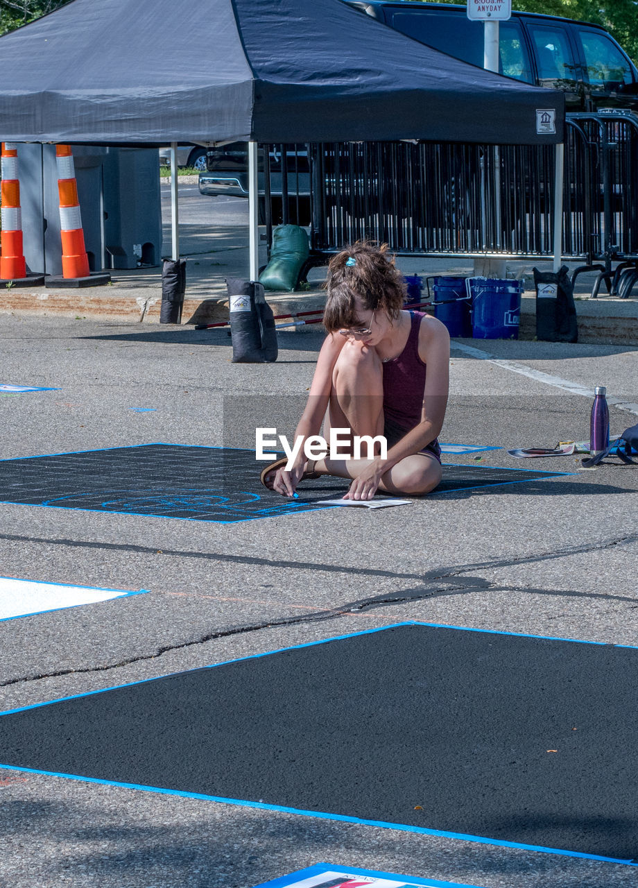 one person, real people, full length, shirtless, day, lifestyles, sitting, architecture, sunlight, built structure, incidental people, road, nature, young adult, city, transportation, leisure activity, sport, men, hairstyle