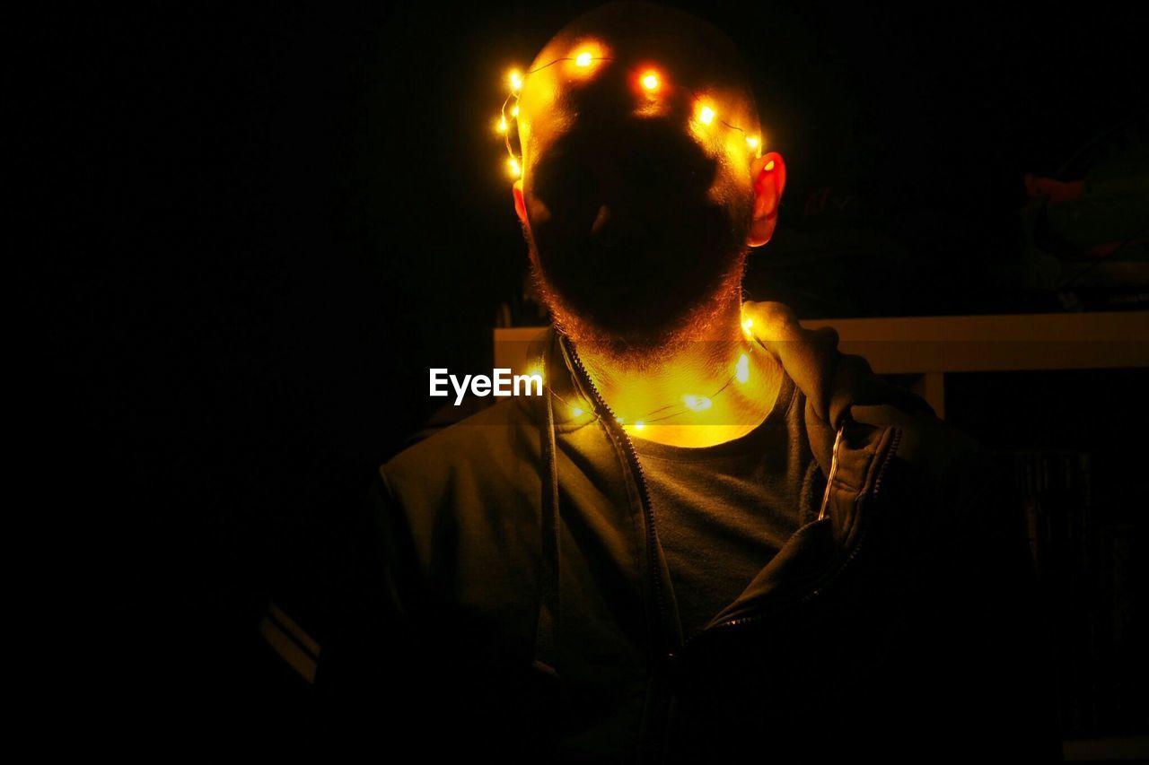 Man with illuminated lighting equipment in darkroom