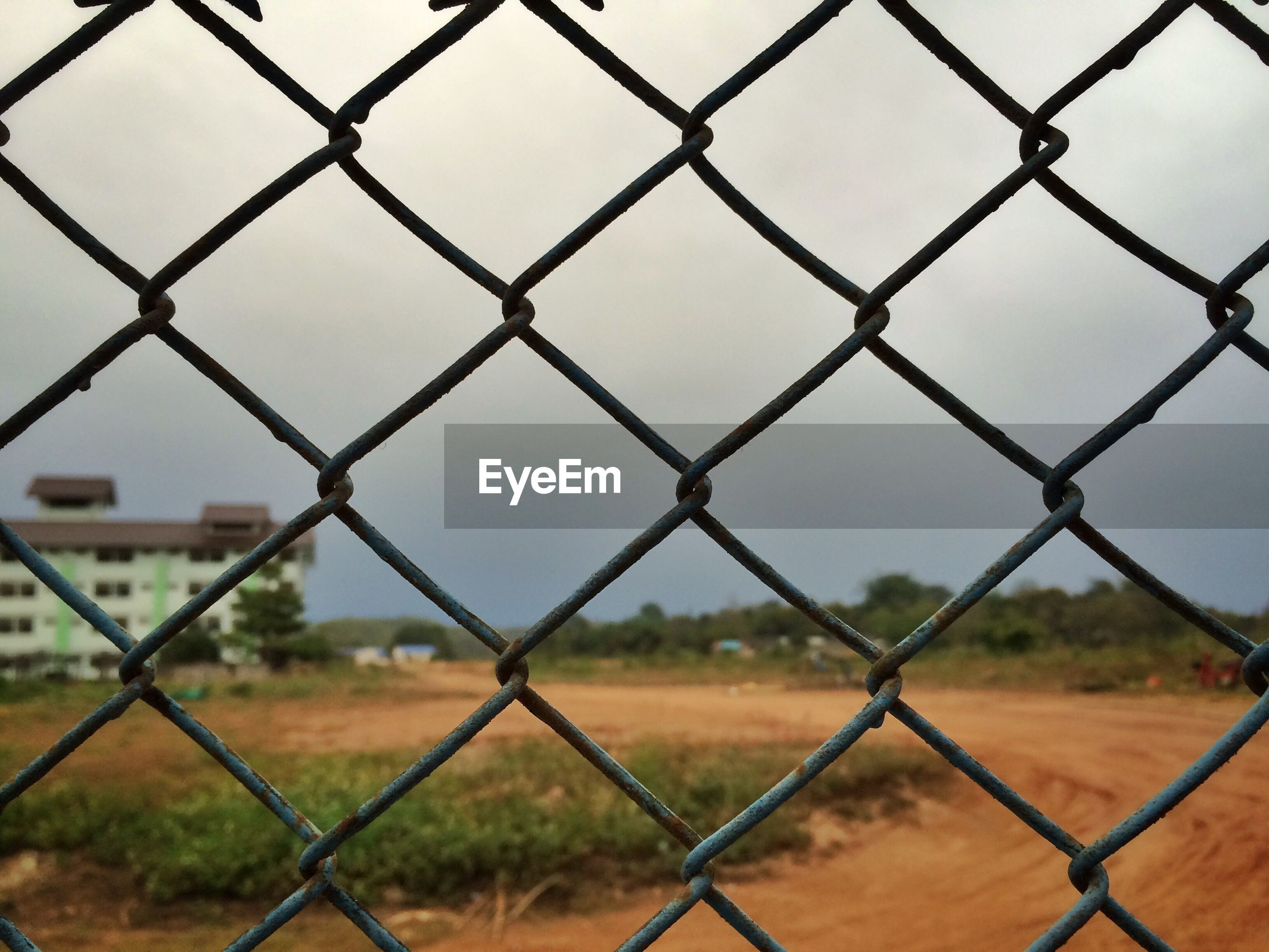 CLOSE-UP OF CHAINLINK FENCE AGAINST SKY IN CITY