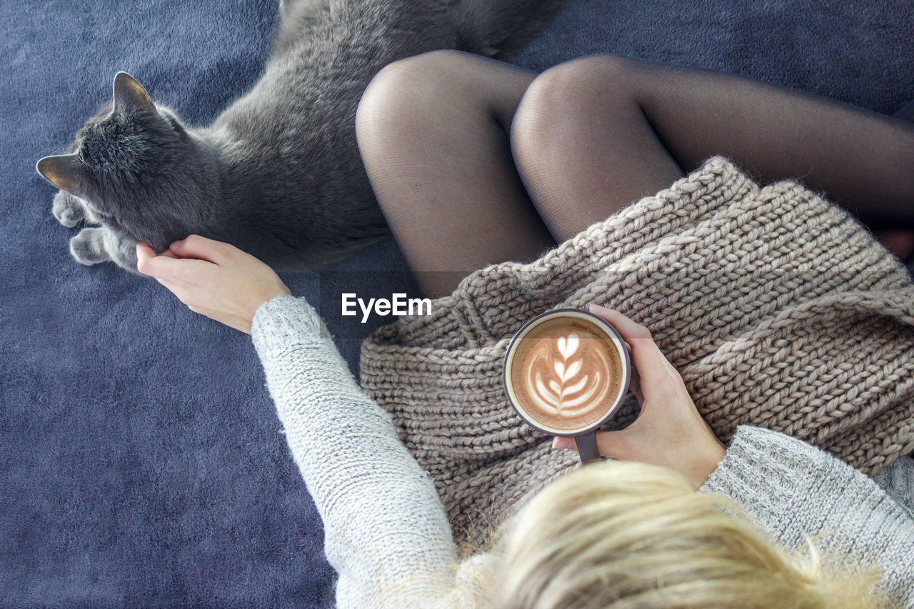 Directly Above Shot Of Woman Holding Coffee While Stroking Cat On Carpet