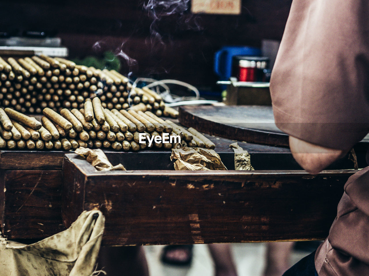Close-up of manual worker making cigar in factory