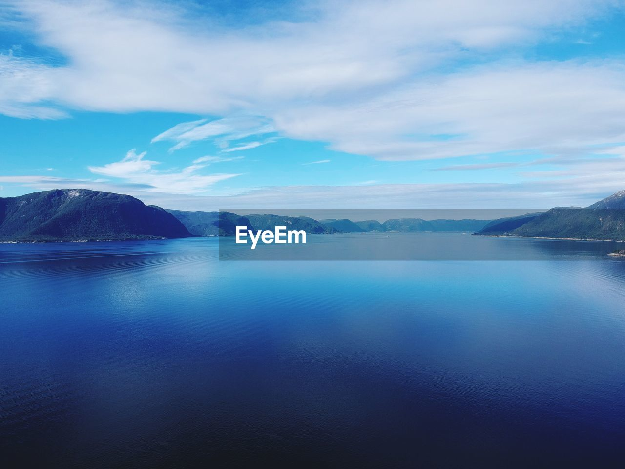 water, scenics - nature, cloud - sky, sky, tranquil scene, beauty in nature, tranquility, mountain, waterfront, nature, lake, day, idyllic, no people, non-urban scene, mountain range, blue, reflection, outdoors
