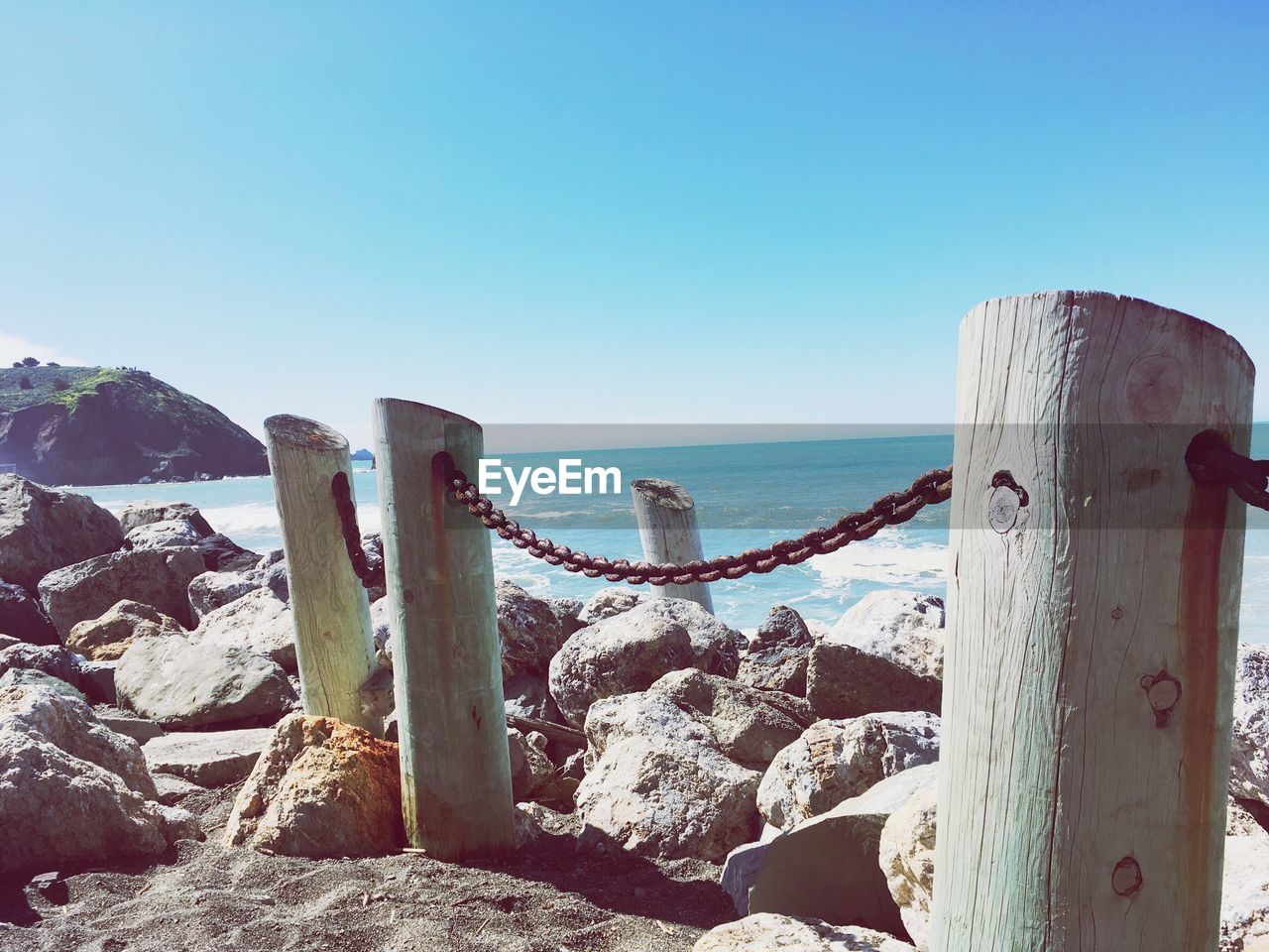 sea, water, horizon over water, clear sky, nature, beauty in nature, tranquil scene, scenics, tranquility, day, no people, sunlight, rock - object, outdoors, beach, blue, sky, wooden post, mountain, close-up