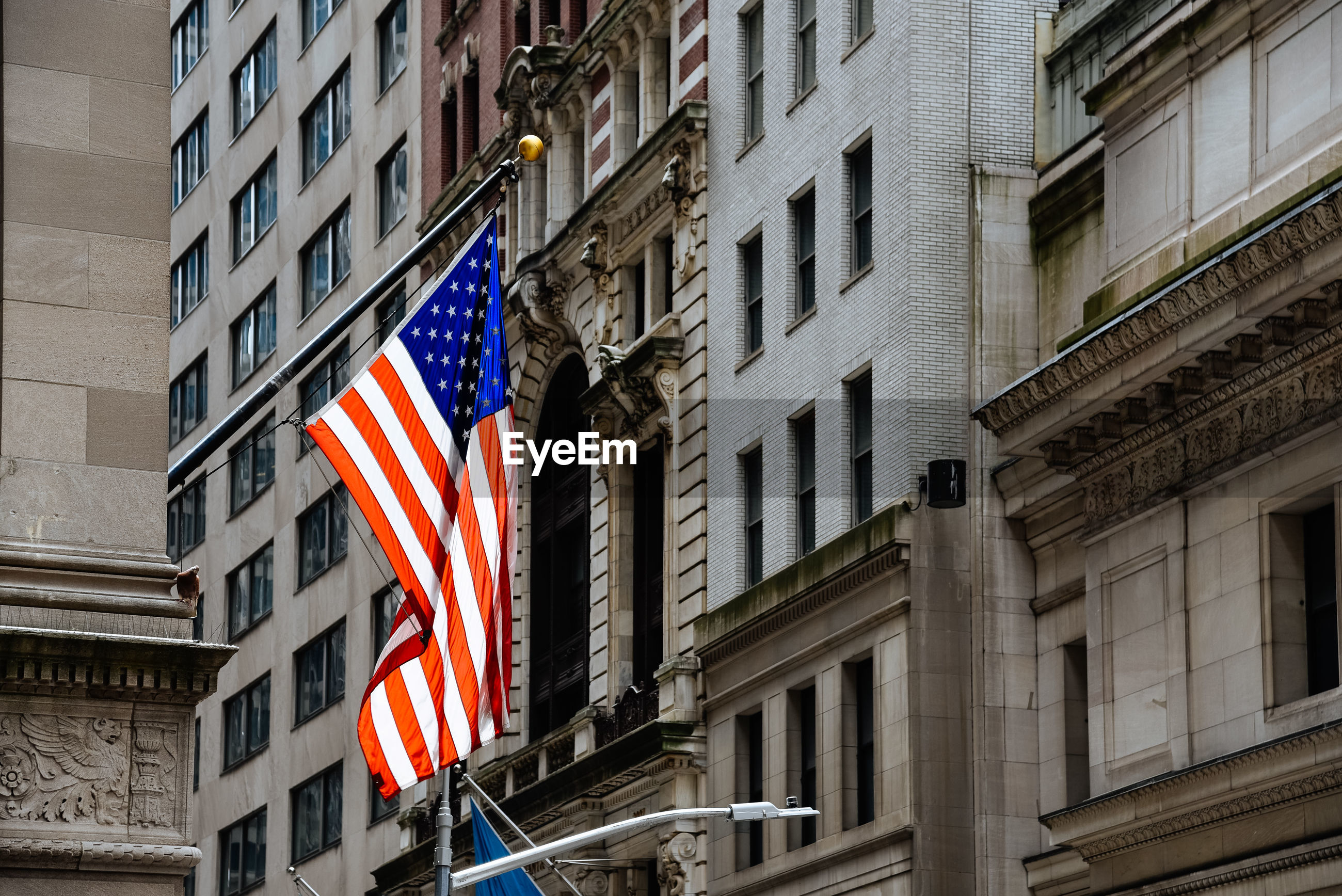 Low angle view of american flag amidst buildings in city