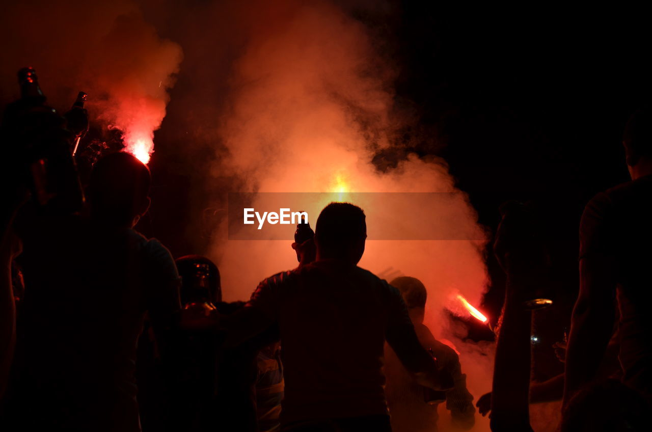 Rear View Of Soccer Fans Celebrating With Fireworks At Night