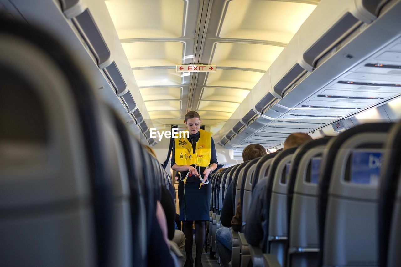 transportation, mode of transportation, vehicle interior, one person, public transportation, indoors, occupation, real people, standing, travel, men, working, rail transportation, young adult, train, vehicle seat, air vehicle, airplane, uniform