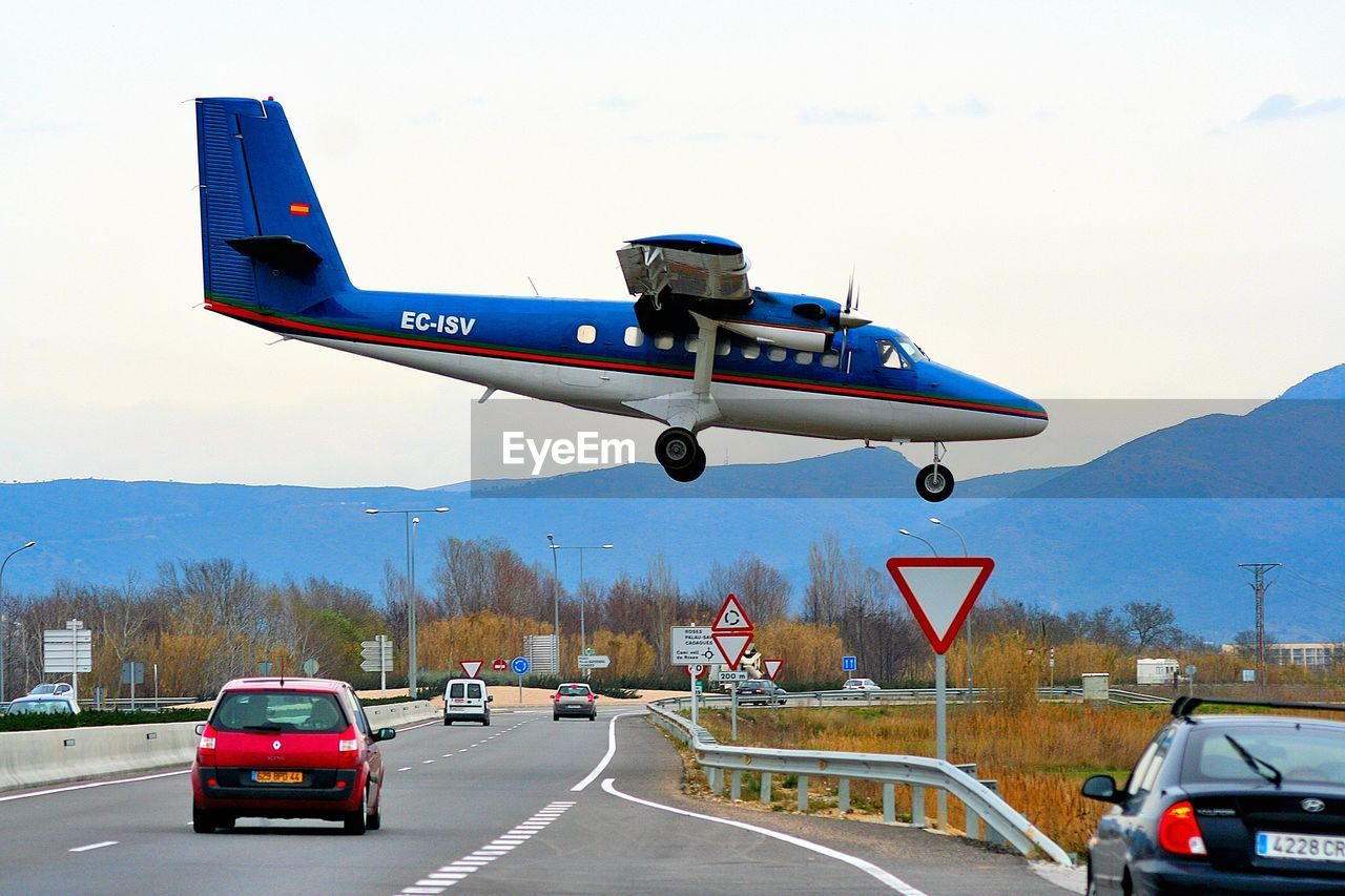 mode of transportation, transportation, air vehicle, sky, airplane, motion, land vehicle, nature, car, road, on the move, motor vehicle, mountain, flying, travel, day, no people, sign, mid-air, street, plane