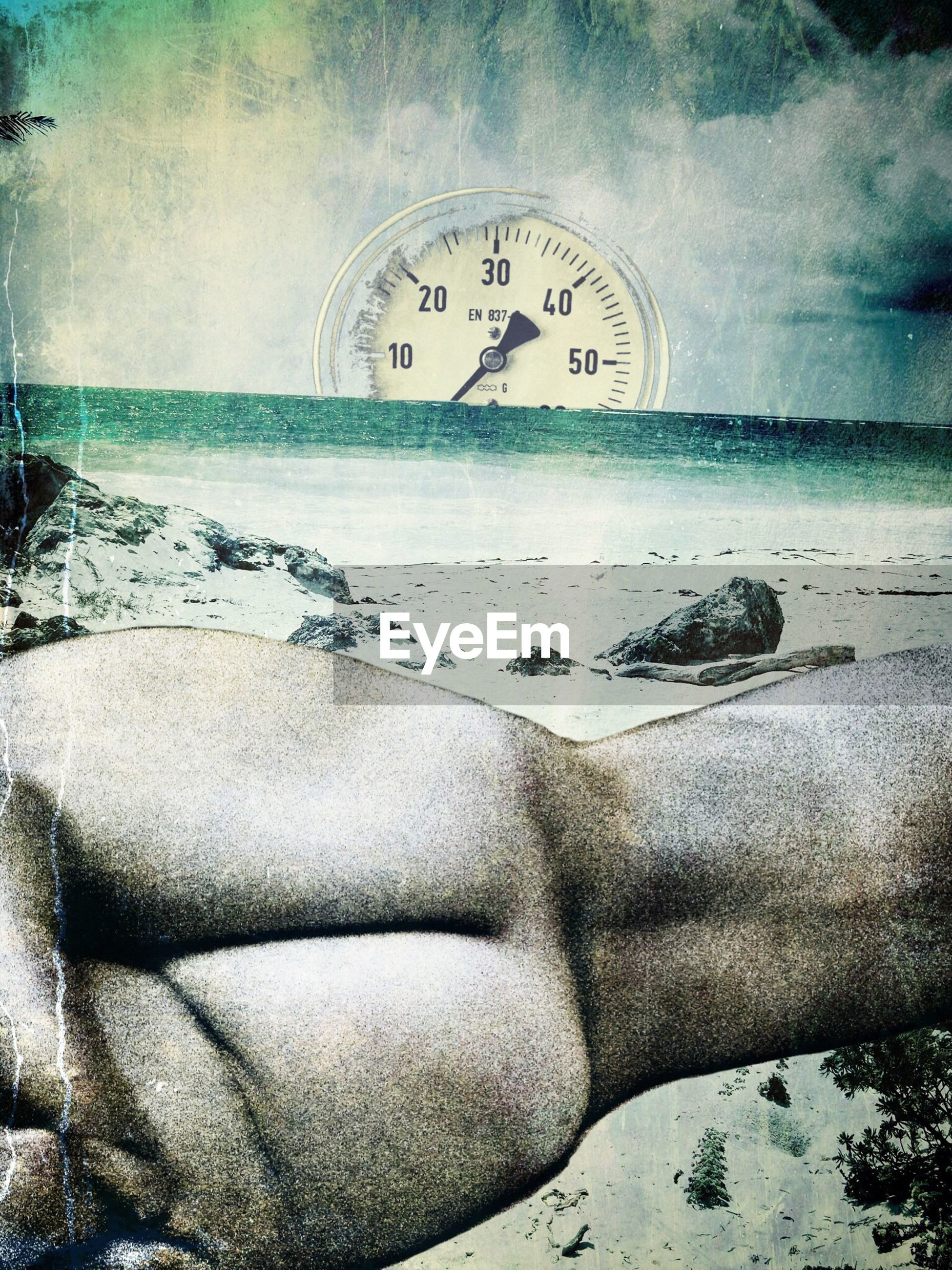 Digital composite image of speedometer and naked woman on beach