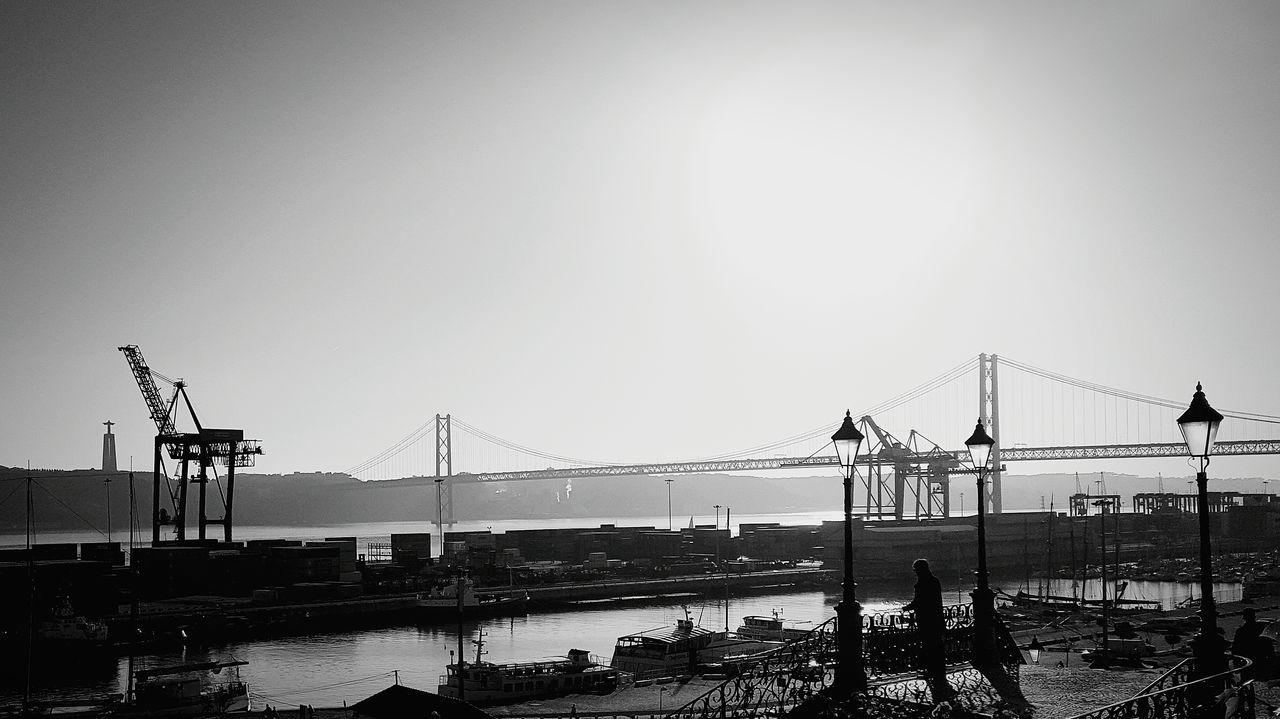 CRANES BY BRIDGE AGAINST SKY