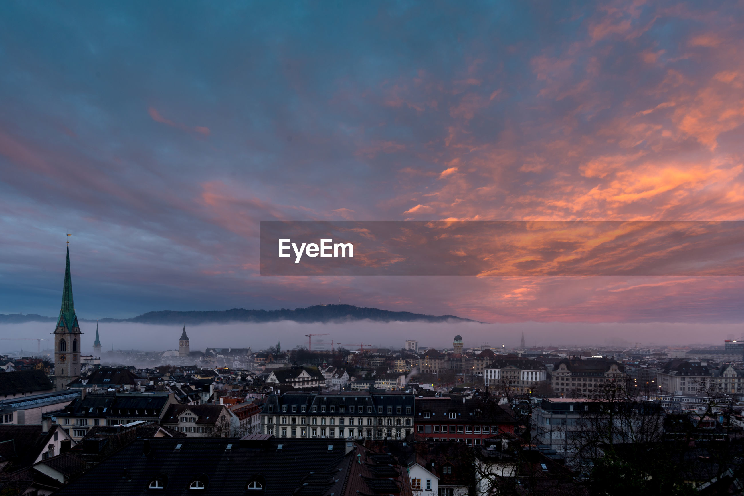 High angle view of townscape against cloudy sky during sunset