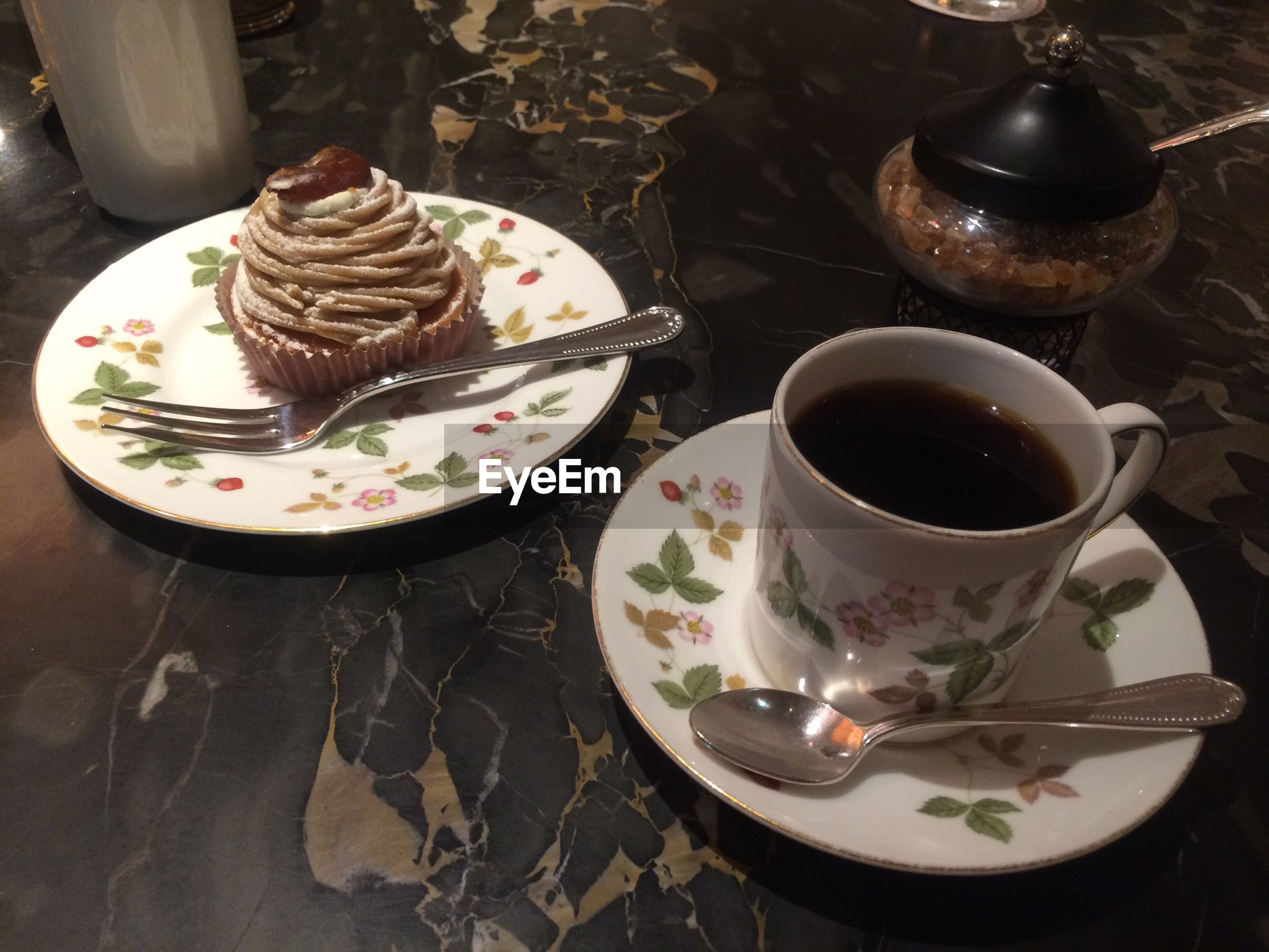 High angle view of cupcake and coffee on floor
