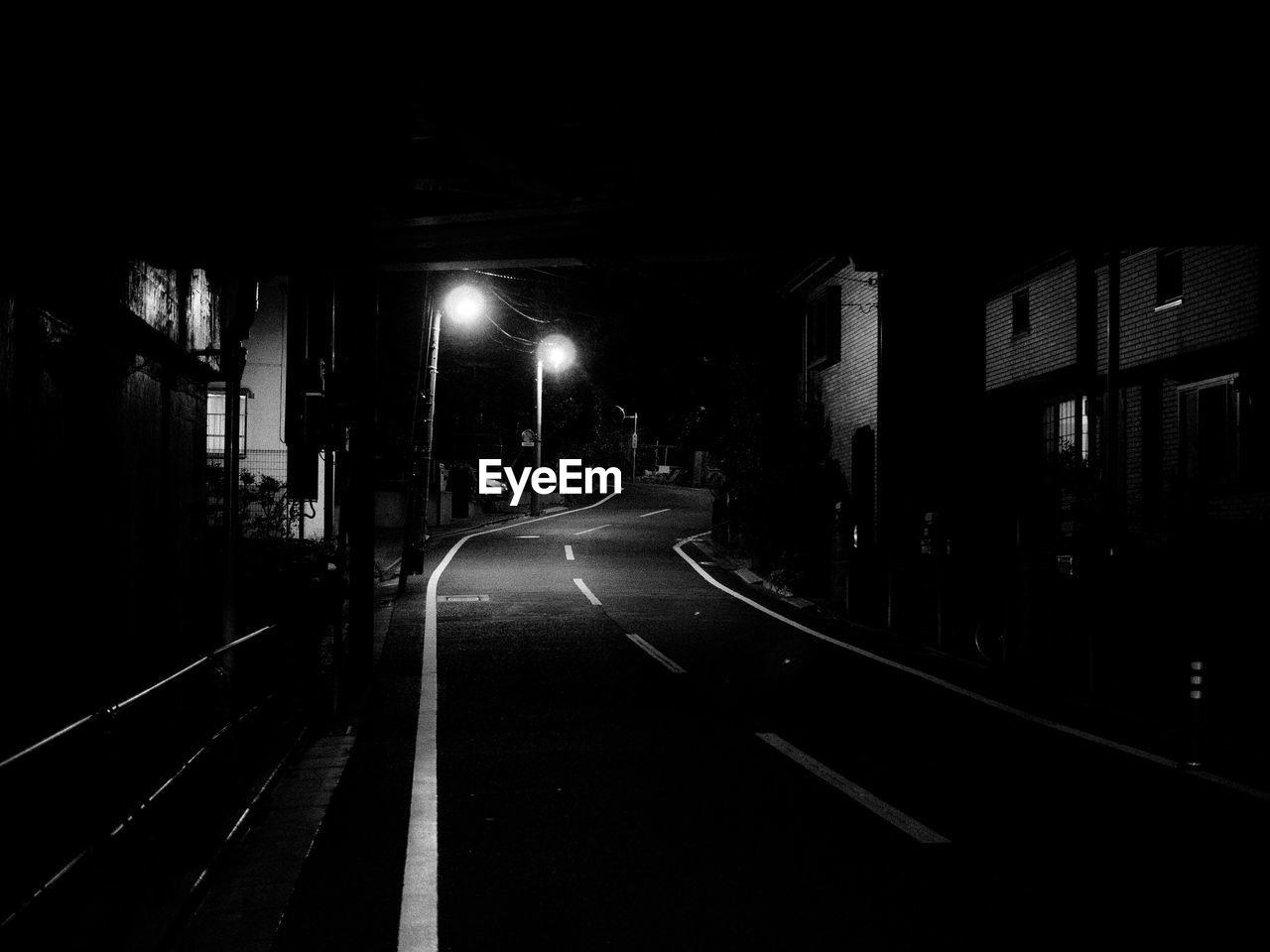 EMPTY ROAD ALONG ILLUMINATED STREET AT NIGHT