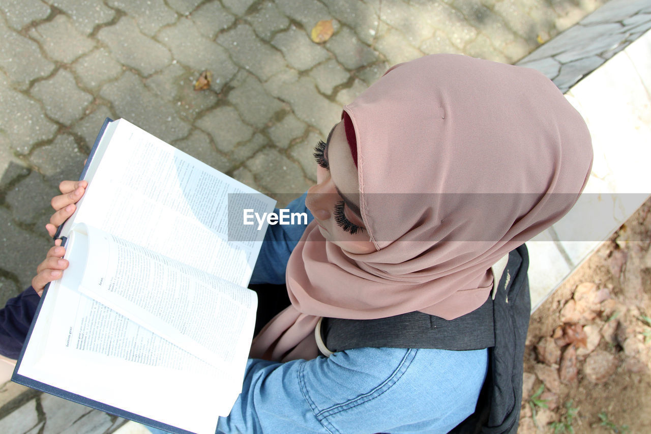 High angle view of woman reading book outdoors
