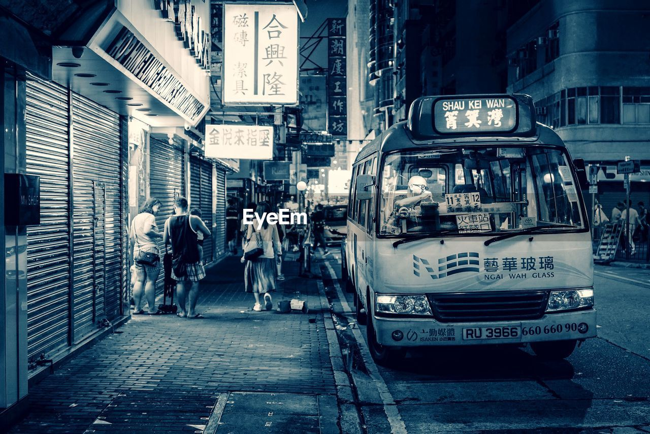 city, architecture, transportation, street, text, real people, building exterior, built structure, mode of transportation, city life, group of people, communication, land vehicle, men, road, walking, people, group, script, incidental people, city street