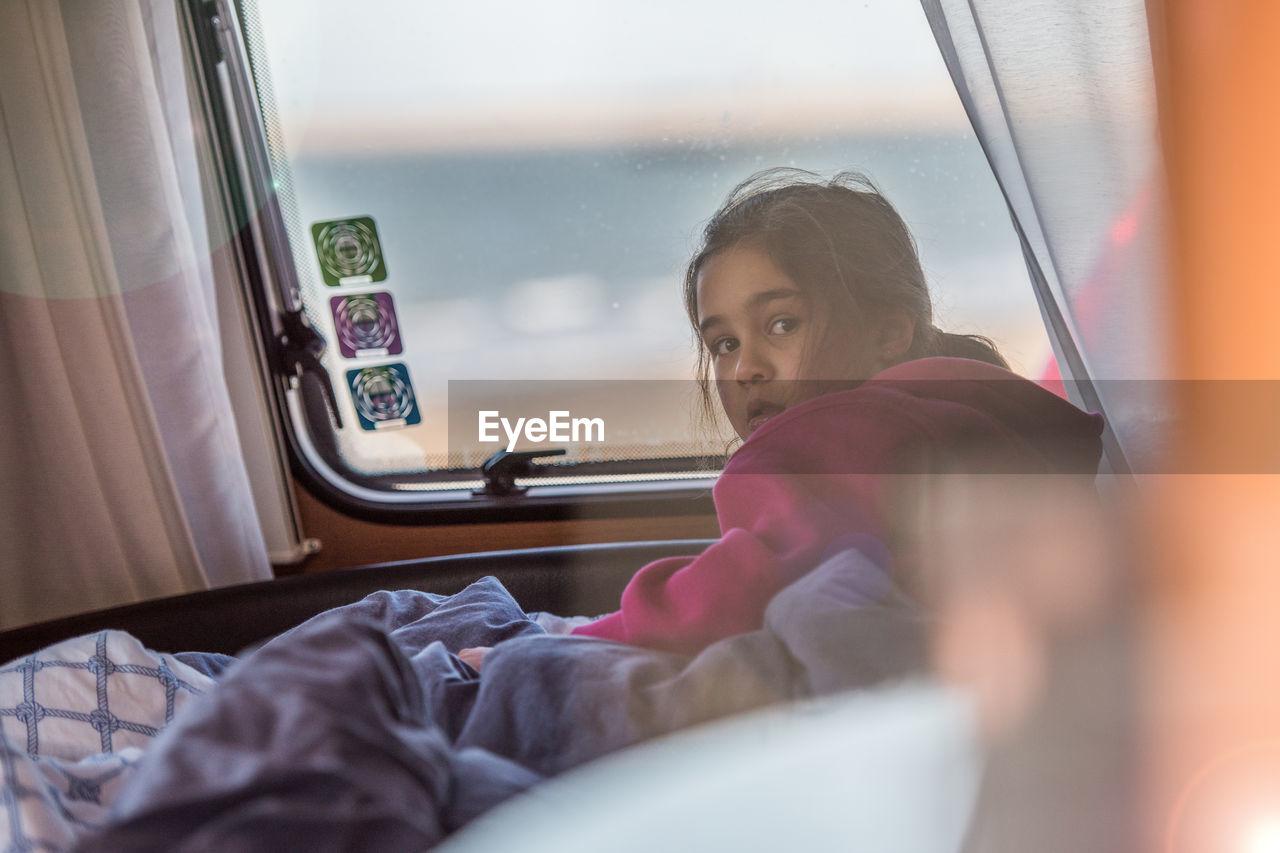 Close-Up Of Girl Sitting In Caravan