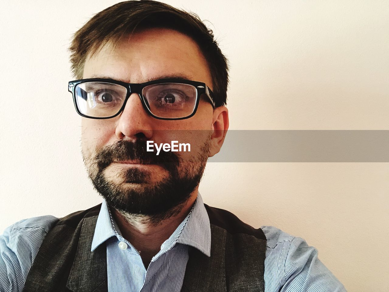 glasses, headshot, front view, beard, one person, portrait, facial hair, eyeglasses, indoors, men, young men, wall - building feature, males, real people, looking at camera, casual clothing, lifestyles, close-up, human face, hairstyle