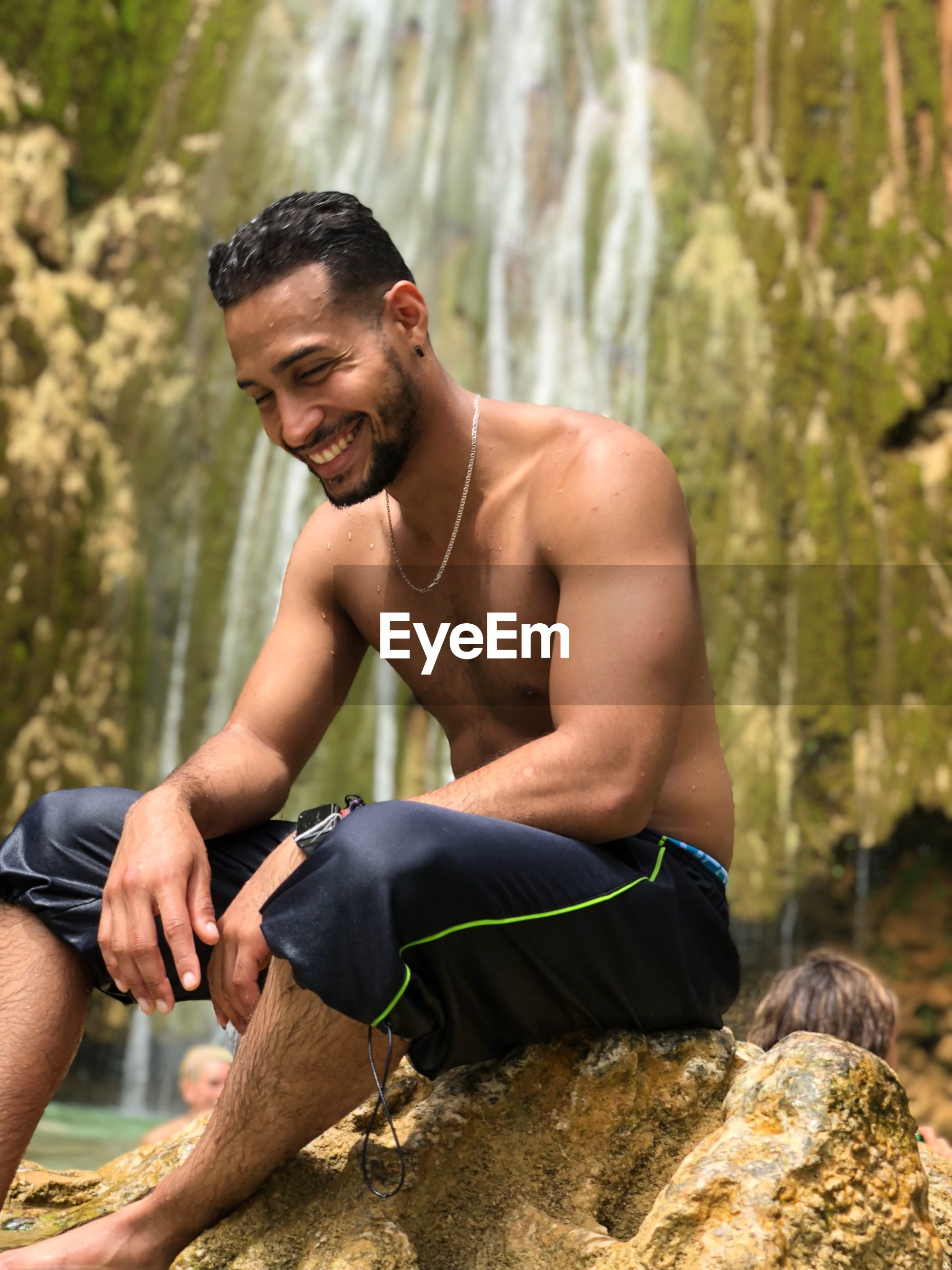 Smiling shirtless young man sitting on rock against waterfall