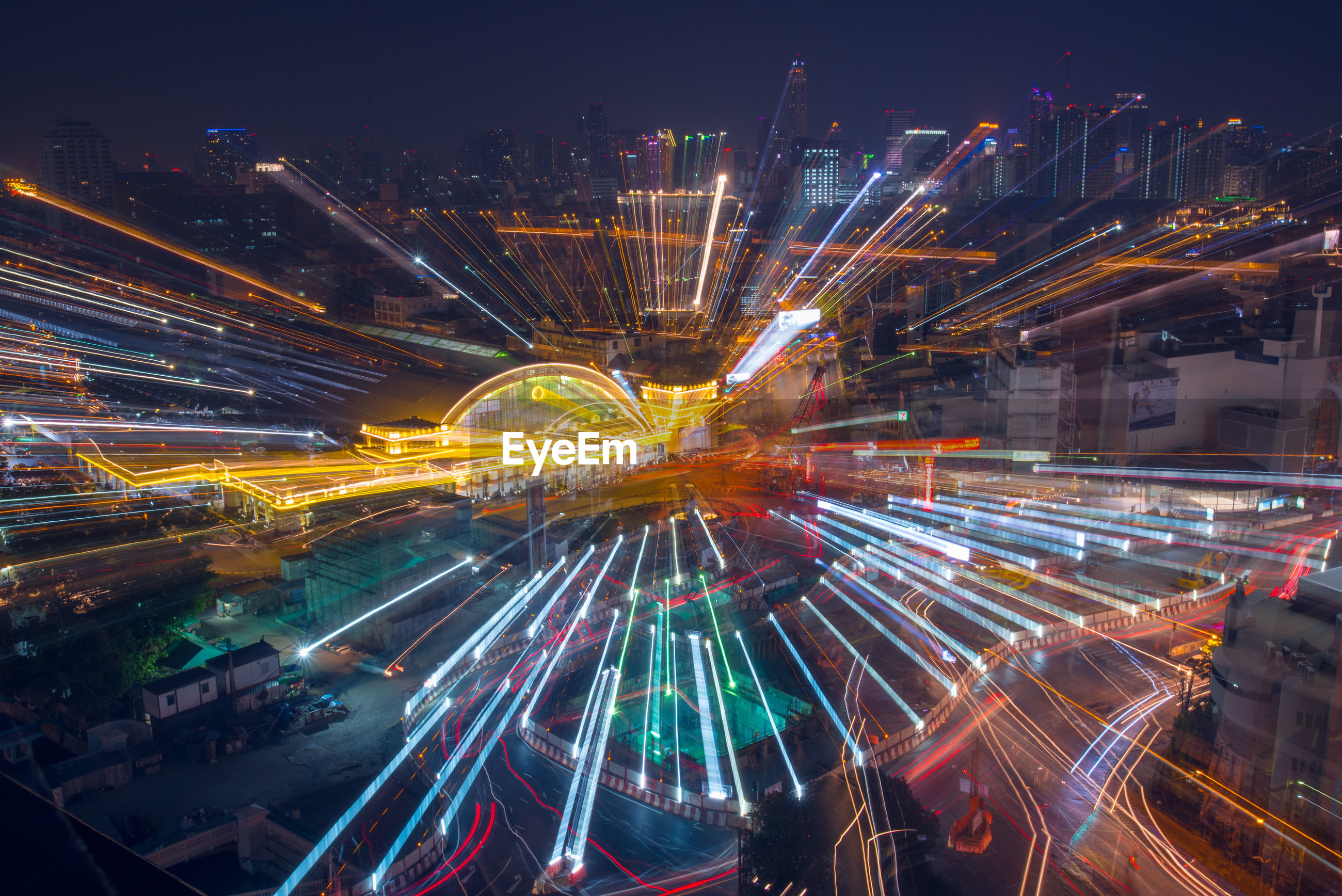 High angle view of light trails in illuminated cityscape at night