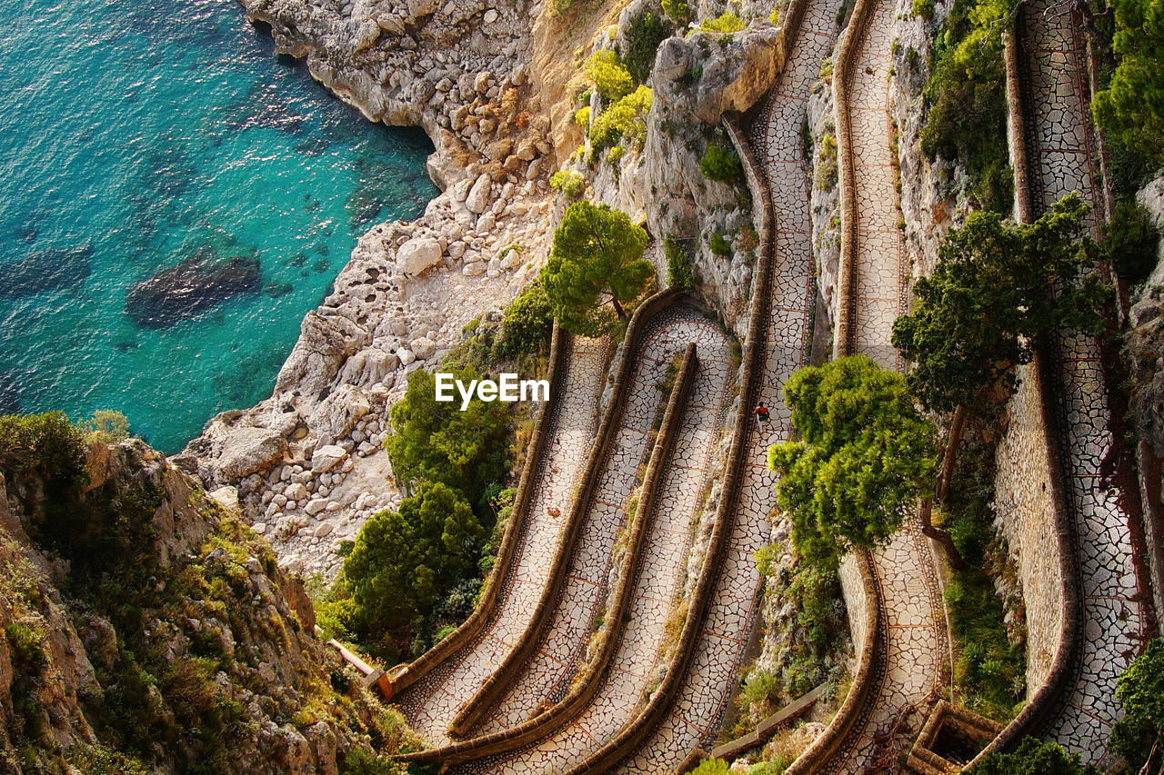 High Angle View Of Narrow Curved Road Against Cropped Sea