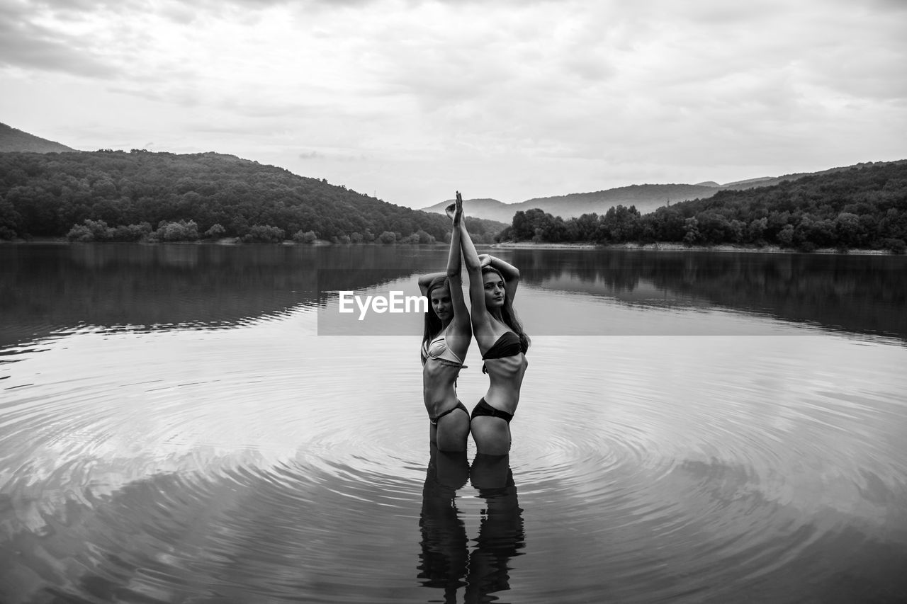 Portrait Of Young Women Standing In Lake Against Sky