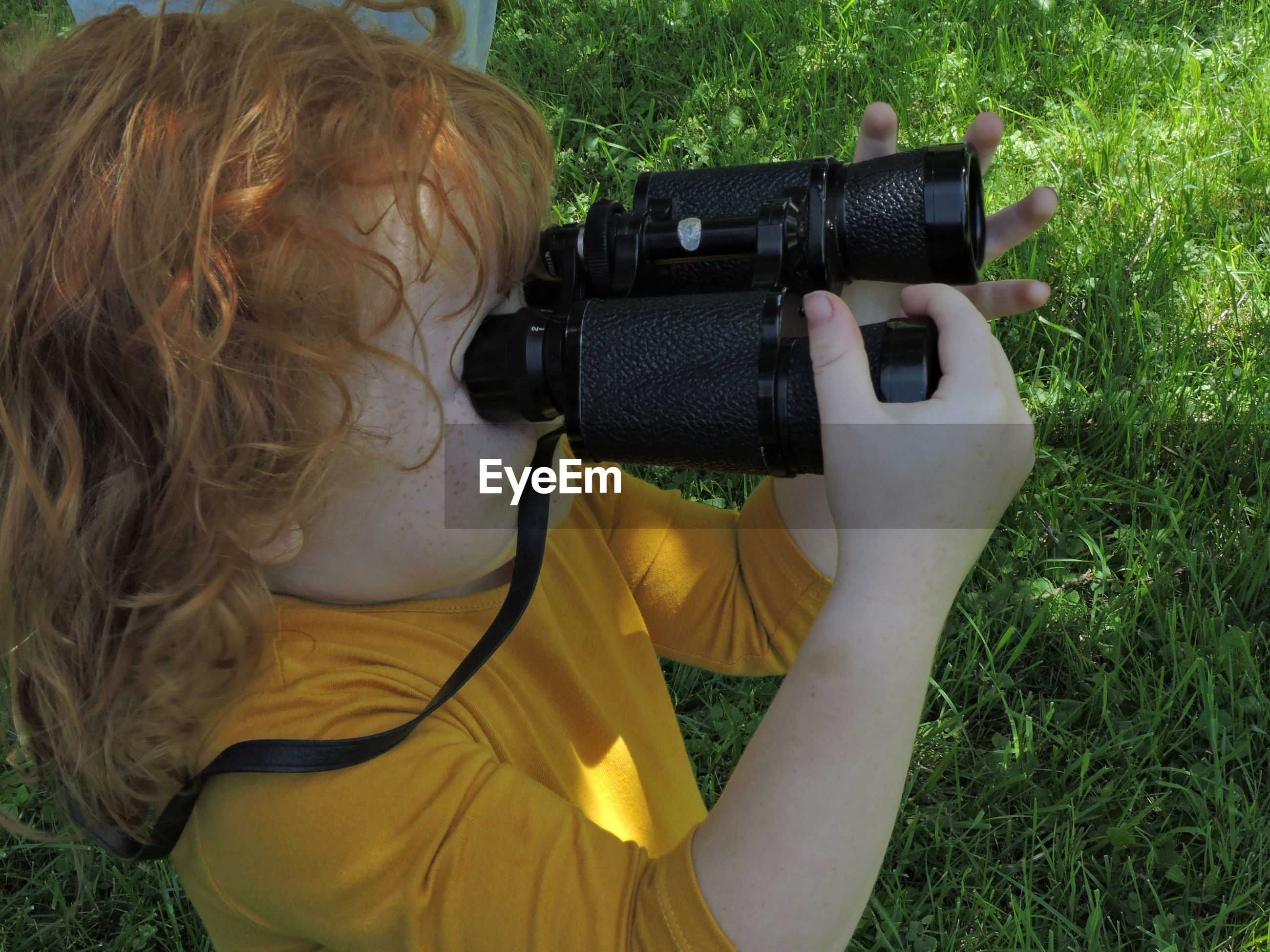 Girl holding binoculars in park