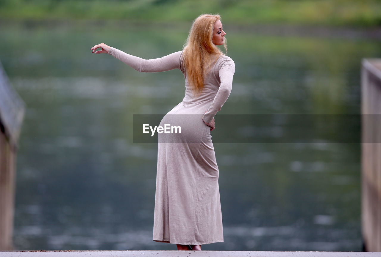 FULL LENGTH OF WOMAN STANDING AGAINST BLURRED WATER