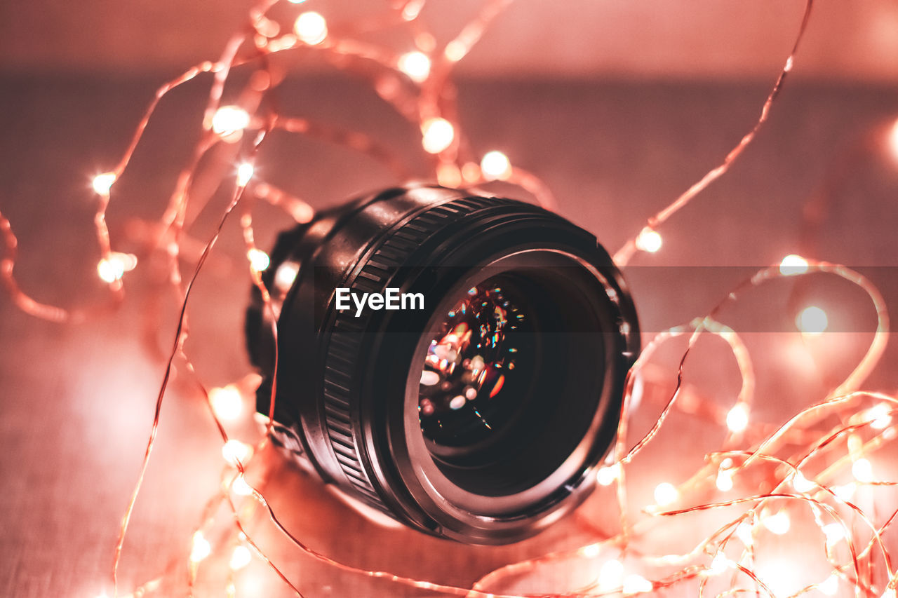 Close-up of camera lens surrounded by illuminated christmas lights at home