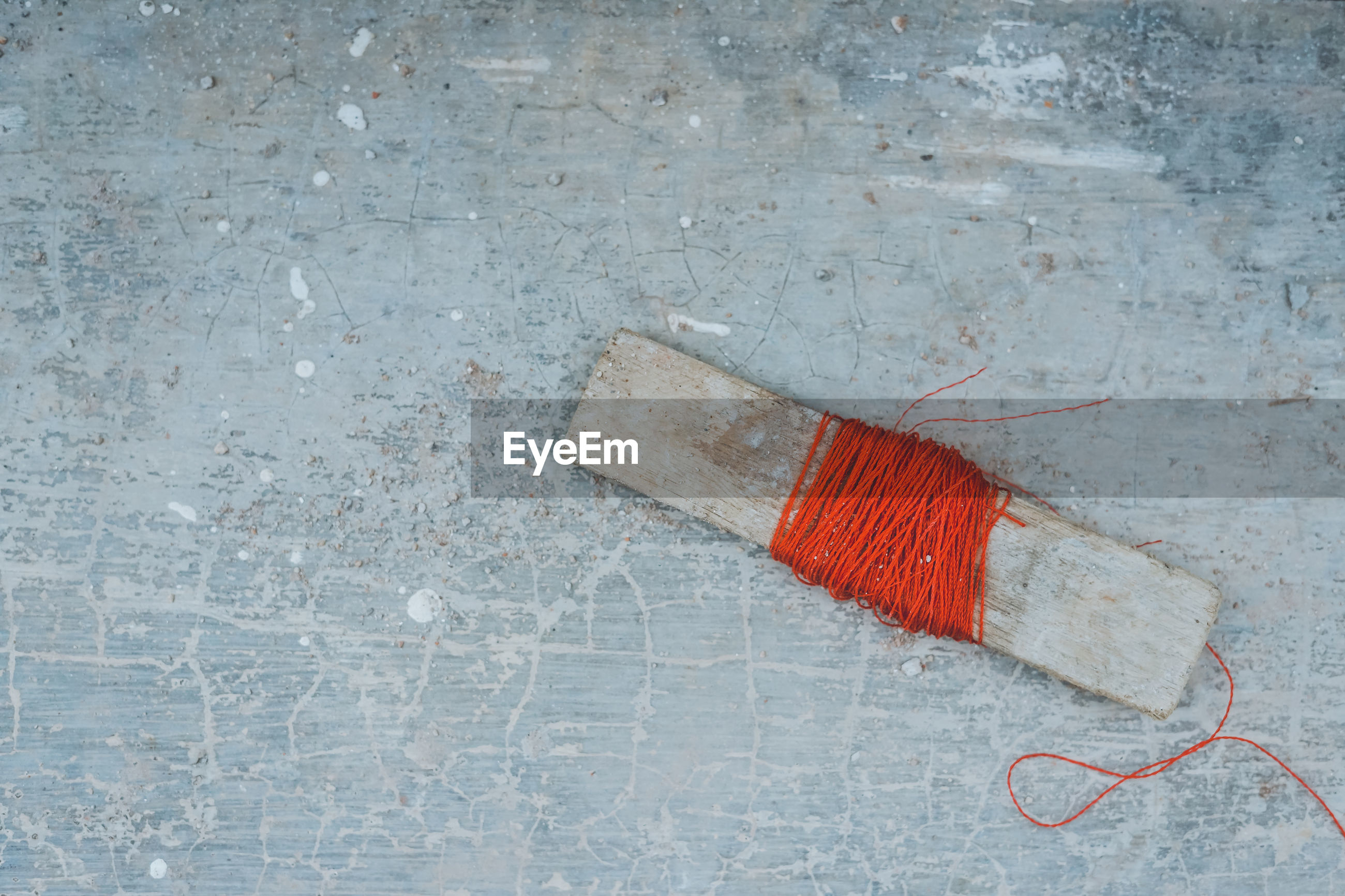 High angle view of red thread wrapped in wood