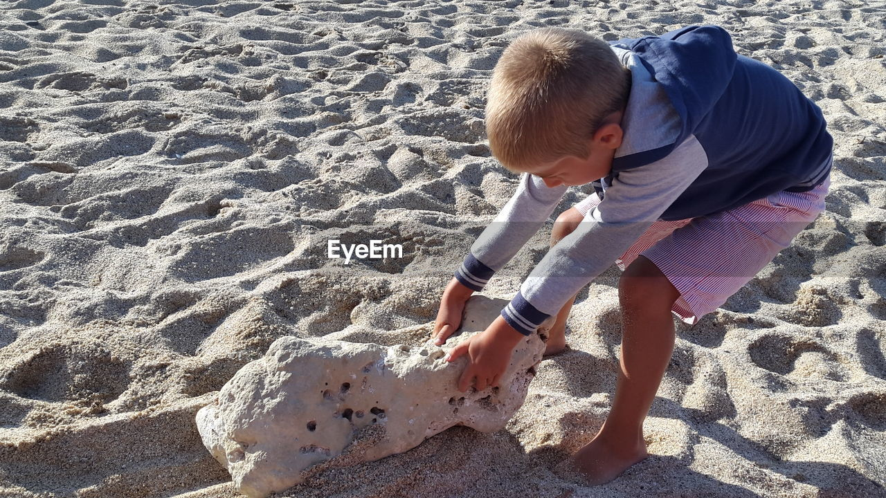 Boy Pulling Rock Formation On Sandy Beach During Sunny Day