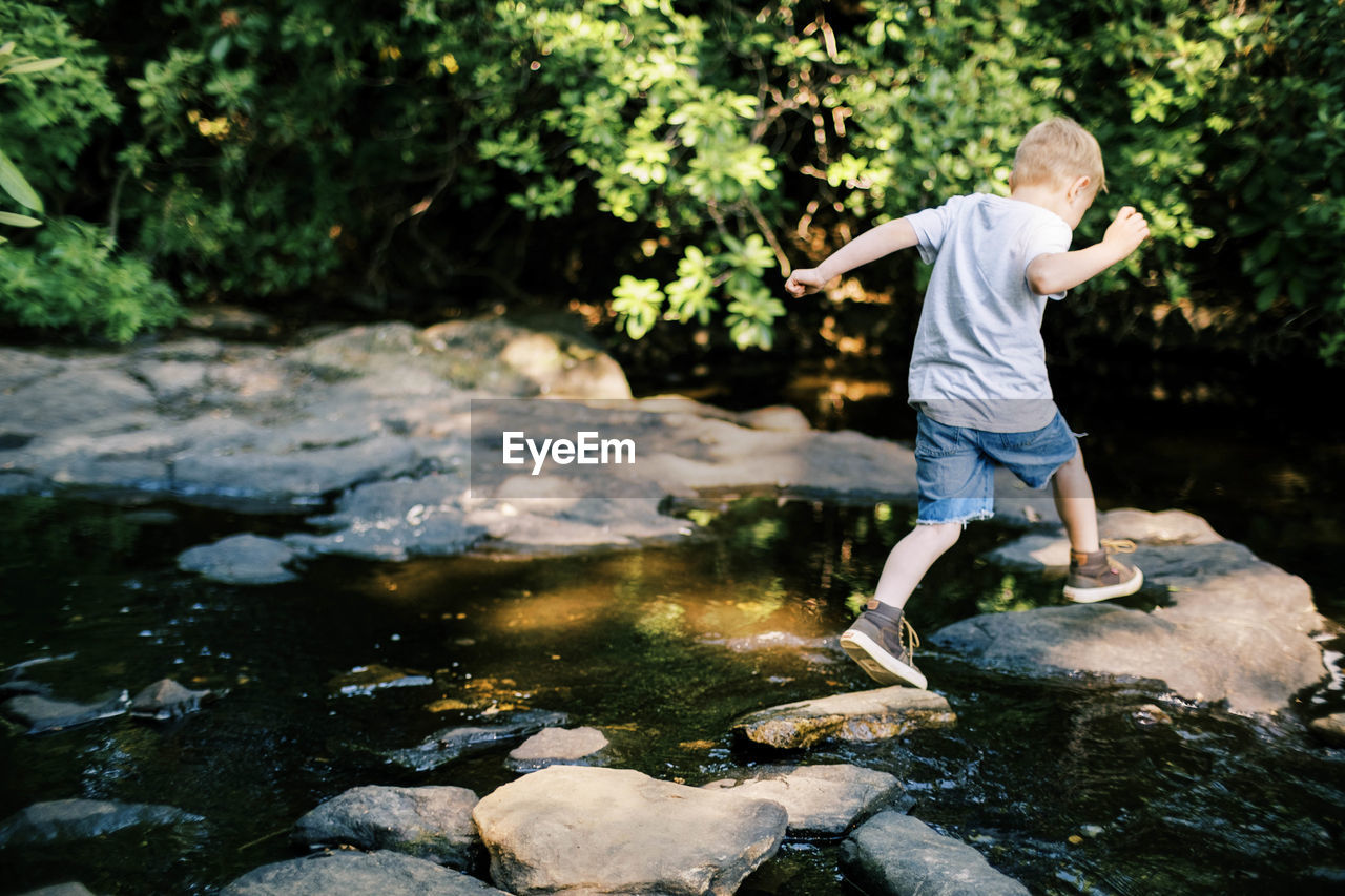 REAR VIEW OF BOY STANDING BY STREAM
