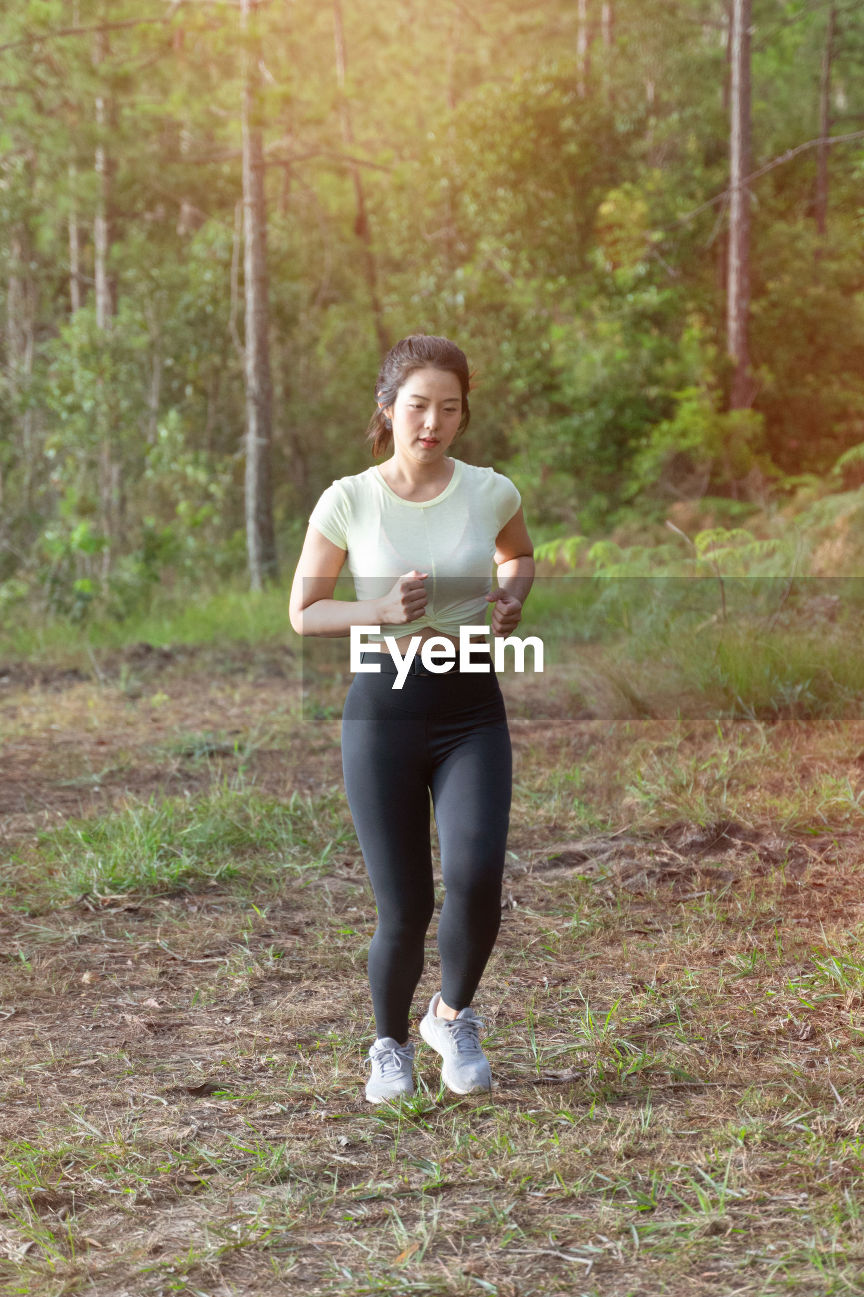 Full length of beautiful woman jogging in forest