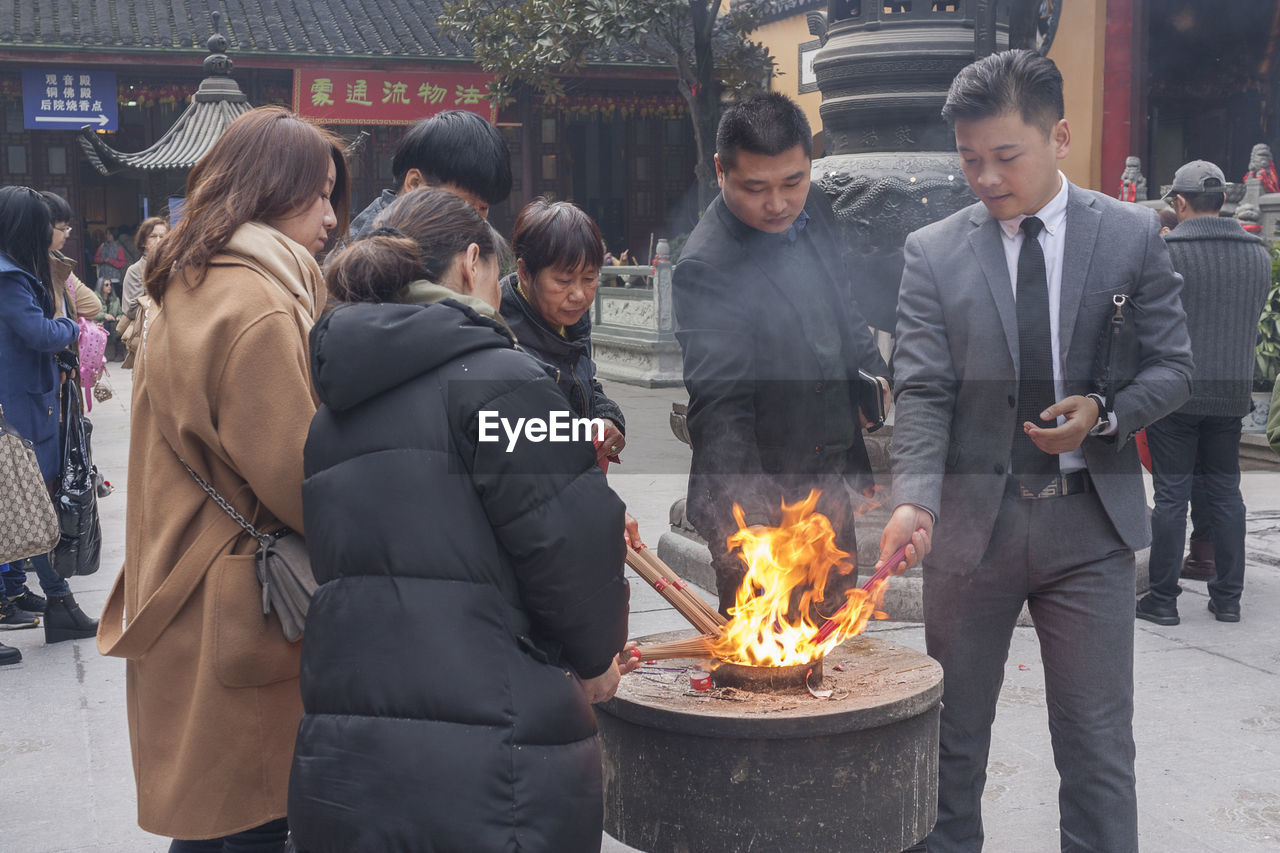 real people, leisure activity, burning, standing, flame, outdoors, lifestyles, togetherness, men, heat - temperature, day, women, young women, architecture, young adult, building exterior, warm clothing, people